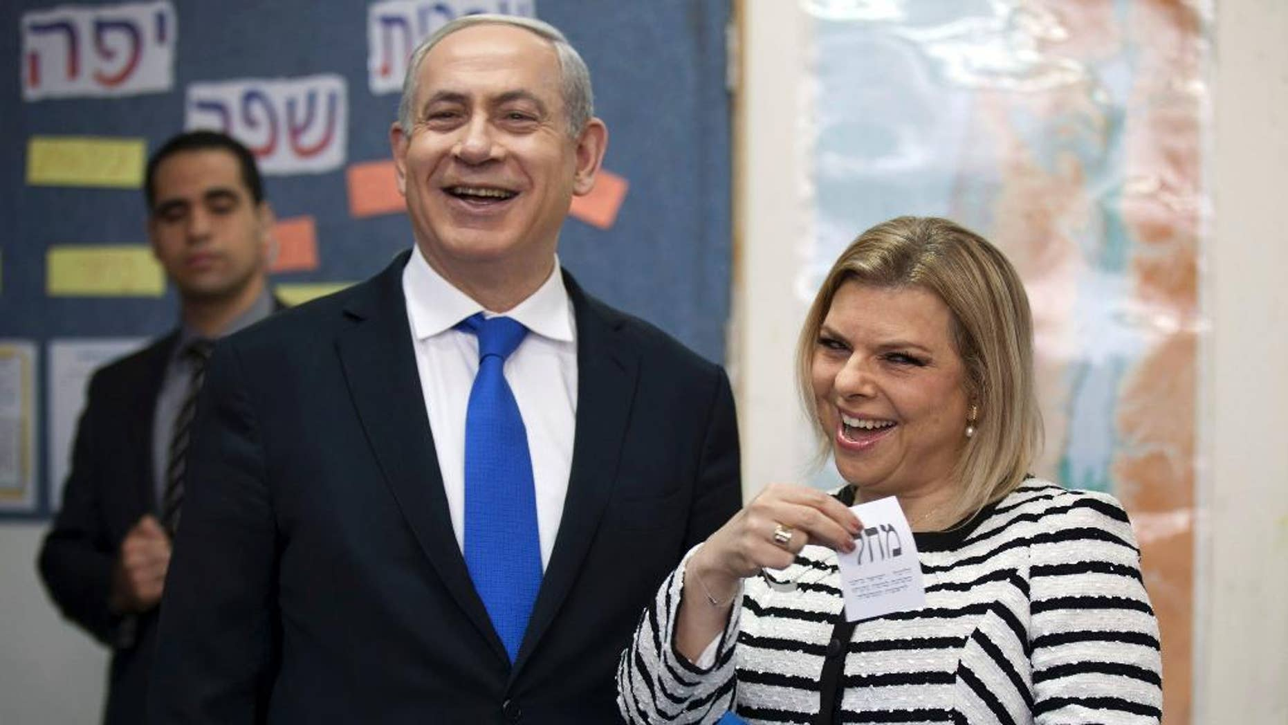 In this Jan. 22, 2013 file photo, Israeli Prime Minister Benjamin Netanyahu stands by his wife Sara as she casts her ballot at a polling station in Jerusalem.
