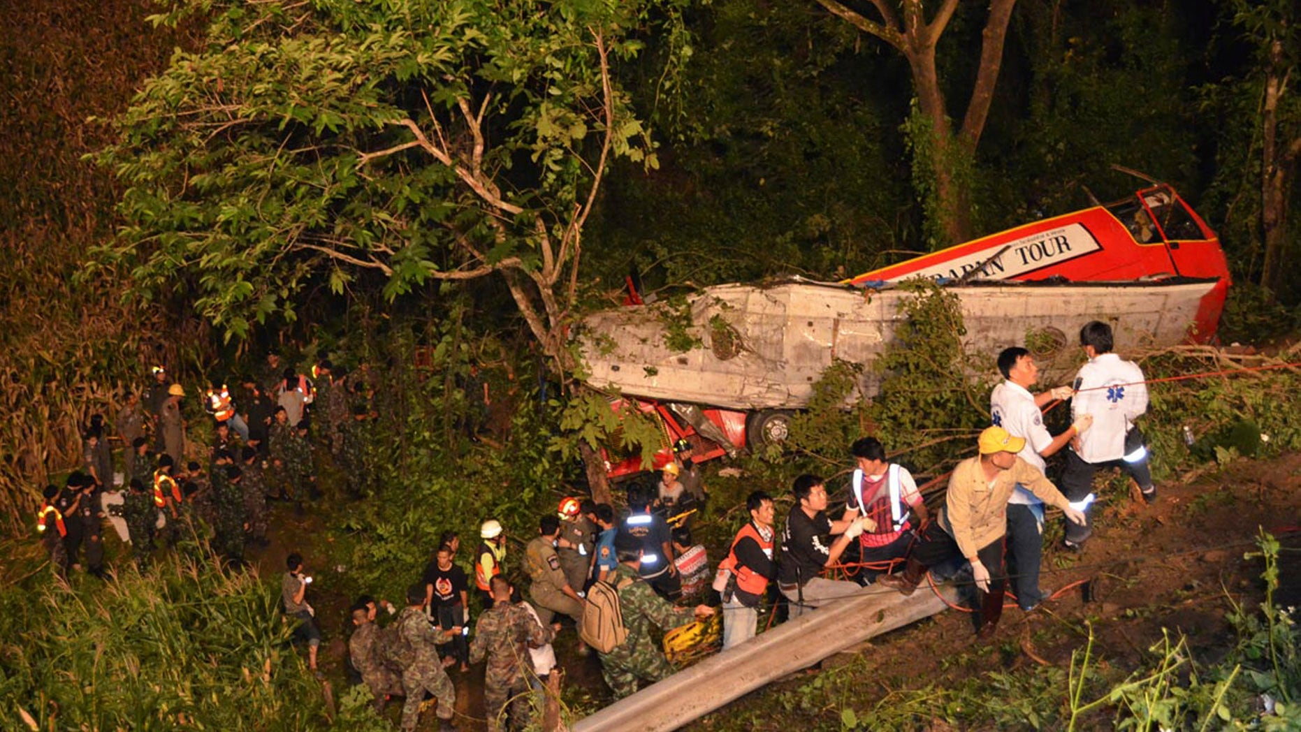In this photo taken Wednesday, Oct. 23, 2013, Thai rescuers search for passengers of a bus that fell about 30 meters (98 feet) into the ravine on a curvy rural road in Lampang province, Thailand. The bus carrying worshippers home from a temple at the end of Buddhist Lent plunged into a ravine in northern Thailand, killing 22 passengers, police said Thursday. (AP Photo/Daily News) THAILAND OUT