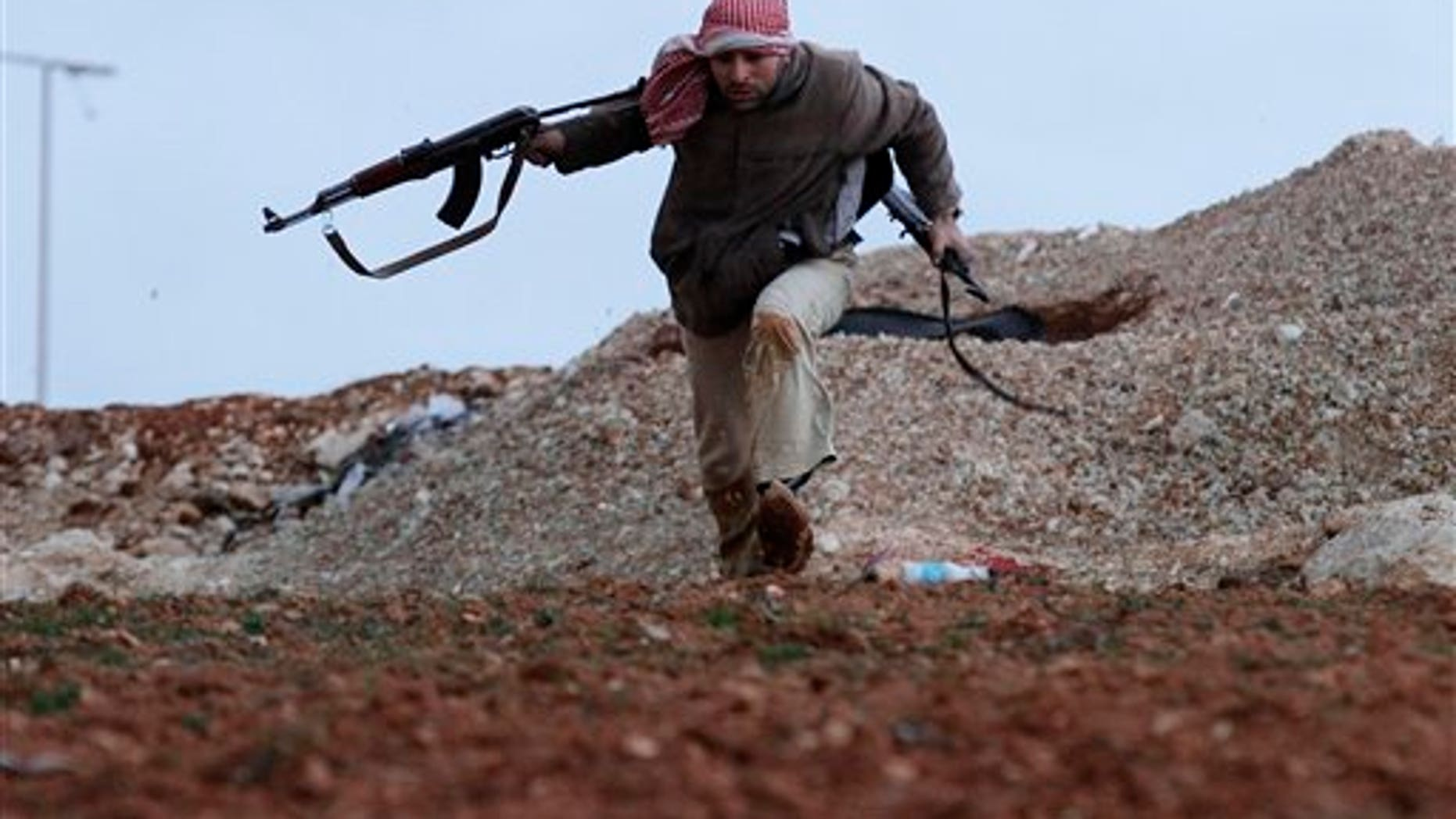 Feb. 8, 2012: A Syrian rebel runs for cover during an exchange of fire with army troops, unseen, in Idlib, Syria.