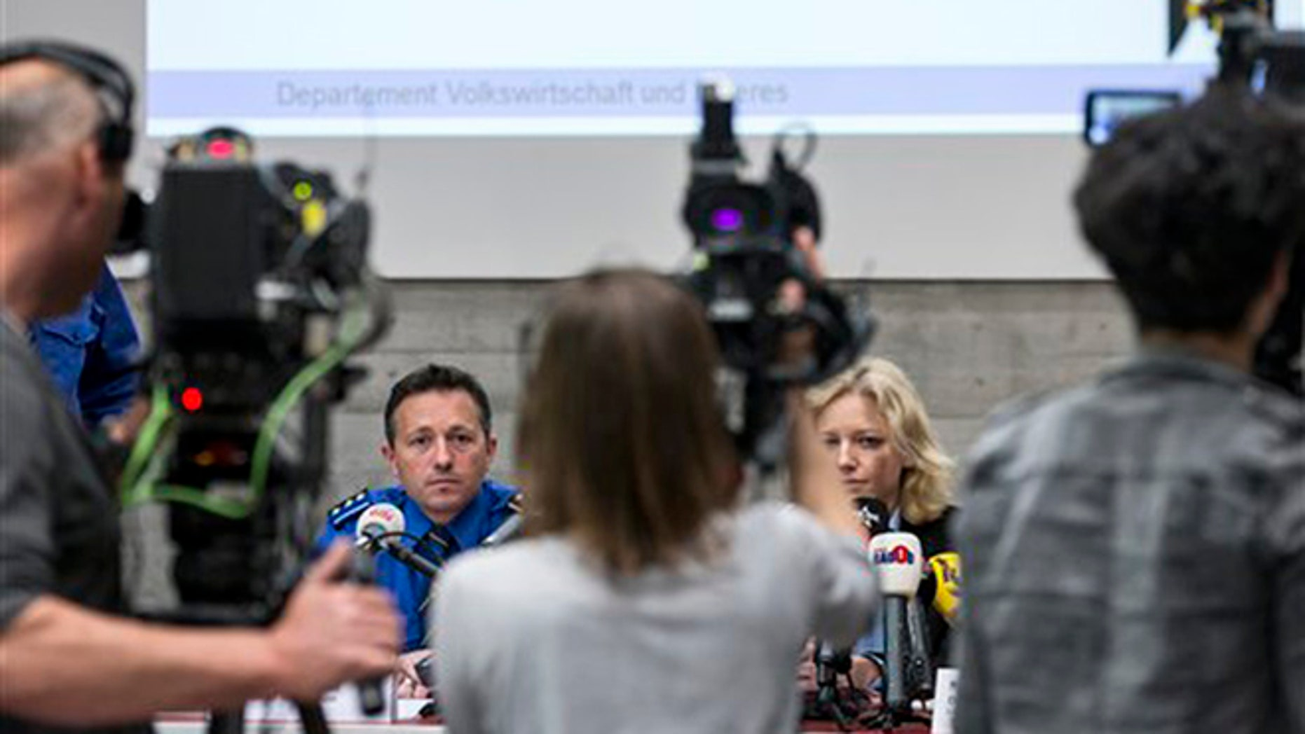 Police captain Markus Gisin, left, and prosecutor Barbara Loppacher, right inform the media in Schafisheim, Switzerland. about the killing of a family in Rupperswil in December. Officials in the nearby Swiss town of Rupperswil are expressing shock after the arrest of a 33-year-old soccer coach over the killing of four people.  (AP)