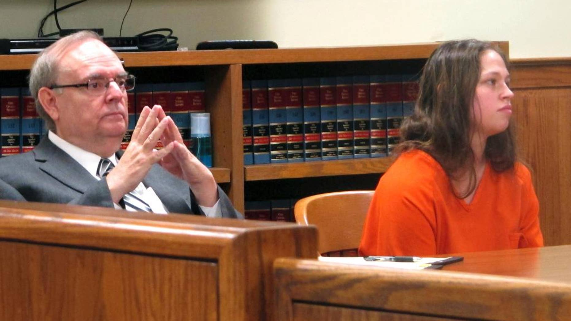 FILE - In this Aug. 20, 2015, file photo, Brittany Pilkington, right, and her attorney, Marc Triplett, listen as a judge sets a bond in Bellefontaine, Ohio. An Ohio judge has delayed the trial of Pilkington, a woman accused of suffocating her three young sons out of jealousy at the attention her husband gave them. The judge granted the extension on Wednesday, Jan. 11, 2017, and ordered all motions to be filed by March 17. (AP Photo/Andrew Welsh-Huggins, File)