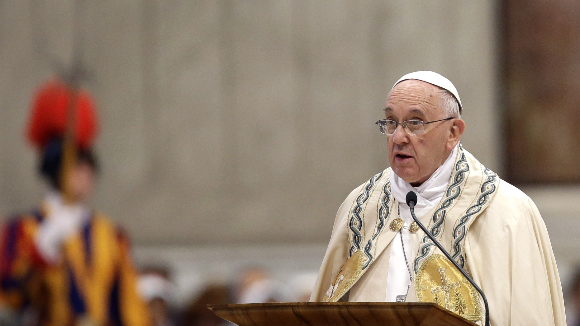 """Pope Francis speaks in St. Peter's Basilica at the Vatican, Saturday, April 11, 2015. Pope Francis has proclaimed a special year of efforts by the Catholic Church to be more merciful and less judgmental. At St. Peter's Basilica Saturday evening, he listened as a Vatican prelate read excerpts from a papal bull, or decree, in which Francis proclaimed an """"Extraordinary Jubilee of Mercy"""" Holy Year. The year begins on Dec. 8 with Francis' opening the normally closed Holy Door in the back of the basilica, and ends on Nov. 20, 2016. (AP Photo/Gregorio Borgia)"""