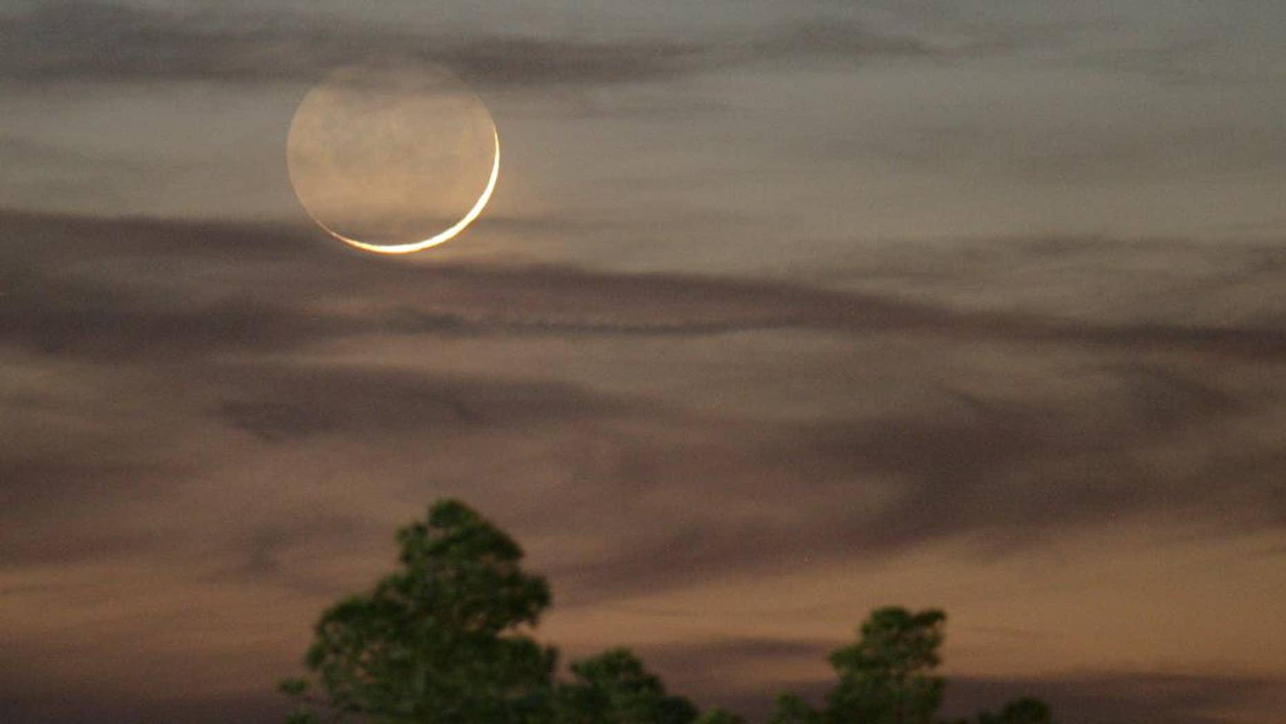 """FILE - In this Jan. 9, 2008, file photo, one day past New, an early Waxing Crescent Moon is seen just after sunset from Tyler, Texas. A rare """"black moon"""" rises over the Western Hemisphere on Friday, Sept. 30, 2016. A black moon is the second new moon in a calendar month. (AP Photo/Dr. Scott M. Lieberman, File)"""