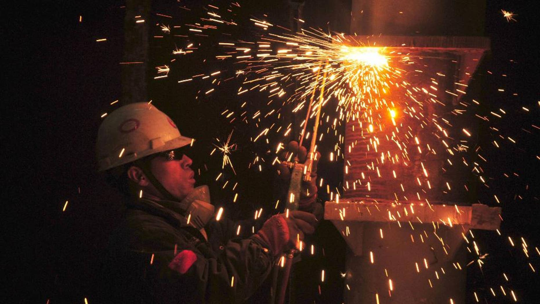 Sparks fly as a welder works in a subsidiary of China Offshore Oil Engineering Co. Ltd. in Qingdao in eastern China's Shandong province Friday, March 31, 2017.  China's factory activity has ticked up again February, 2017, to its highest level in nearly five years, in a fresh sign the world's No. 2 economy is picking up steam. The official purchasing managers' index released Friday climbed to 51.8 in March from 51.6 in the previous month.(Chinatopix via AP)