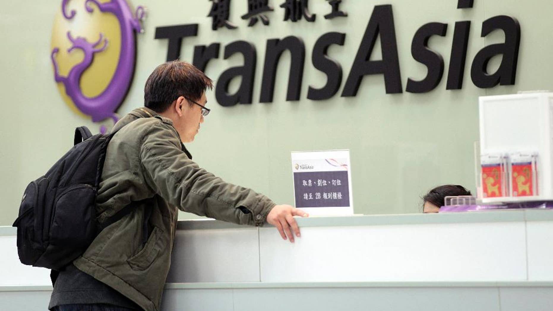 FILE- In this Saturday, Feb. 7, 2015, file photo, a passenger waits at the ticket counter of TransAsia Airways at the Songshan Airport in Taipei, Taiwan. Taiwanese airline TransAsia has announced it is shutting down following financial losses and two fatal crashes. TransAsia chairman Vincent Lin said Tuesday the airline, which served cities in China, Japan and Southeast Asia, was unable to reverse widening losses or raise additional money. (AP Photo/Wally Santana, File)