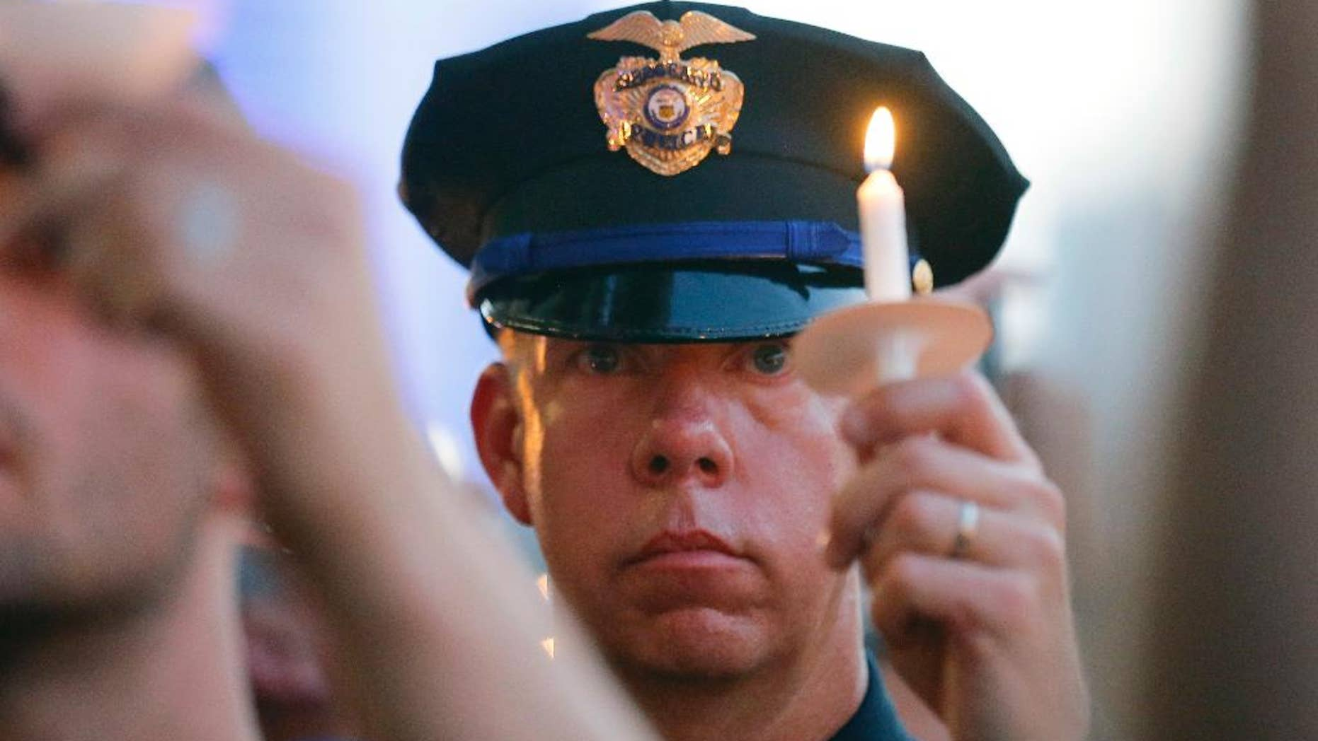 A police officers takes part in a candle light vigil at City Hall, Monday, July 11, 2016, in Dallas. Five police officers were killed and several injured during a shooting in downtown Dallas last Thursday night. (AP Photo/Tony Gutierrez)