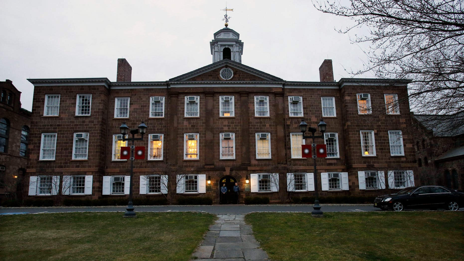 At dusk, lights remain on at Rutgers University's Old Queens building where  President Robert Barchi was in a meeting Thursday, April 4, 2013, in New Brunswick, N.J., one day after Rutgers basketball head coach Mike Rice was fired. Rice was fired Wednesday after a videotape aired showing Rice using gay slurs, shoving and grabbing his players and throwing balls at them in practice. Scarlet Knights AD Tim Pernetti was given a copy of the video in late November by a disgruntled former employee, and he suspended Rice for three games, fined him $50,000 and made him undergo anger management classes for inappropriate behavior after investigating it. (AP Photo/Mel Evans)