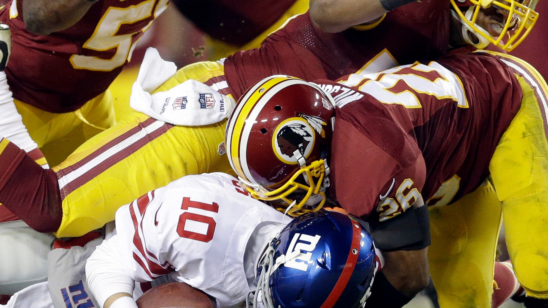 New York Giants quarterback Eli Manning (10) is sacked by Washington Redskins inside linebacker London Fletcher (59), outside linebacker Rob Jackson (50)  and cornerback Josh Wilson during the second half of an NFL football game Sunday, Dec. 1, 2013, in Landover, Md. The Giants won 24-17. (AP Photo/Patrick Semansky)