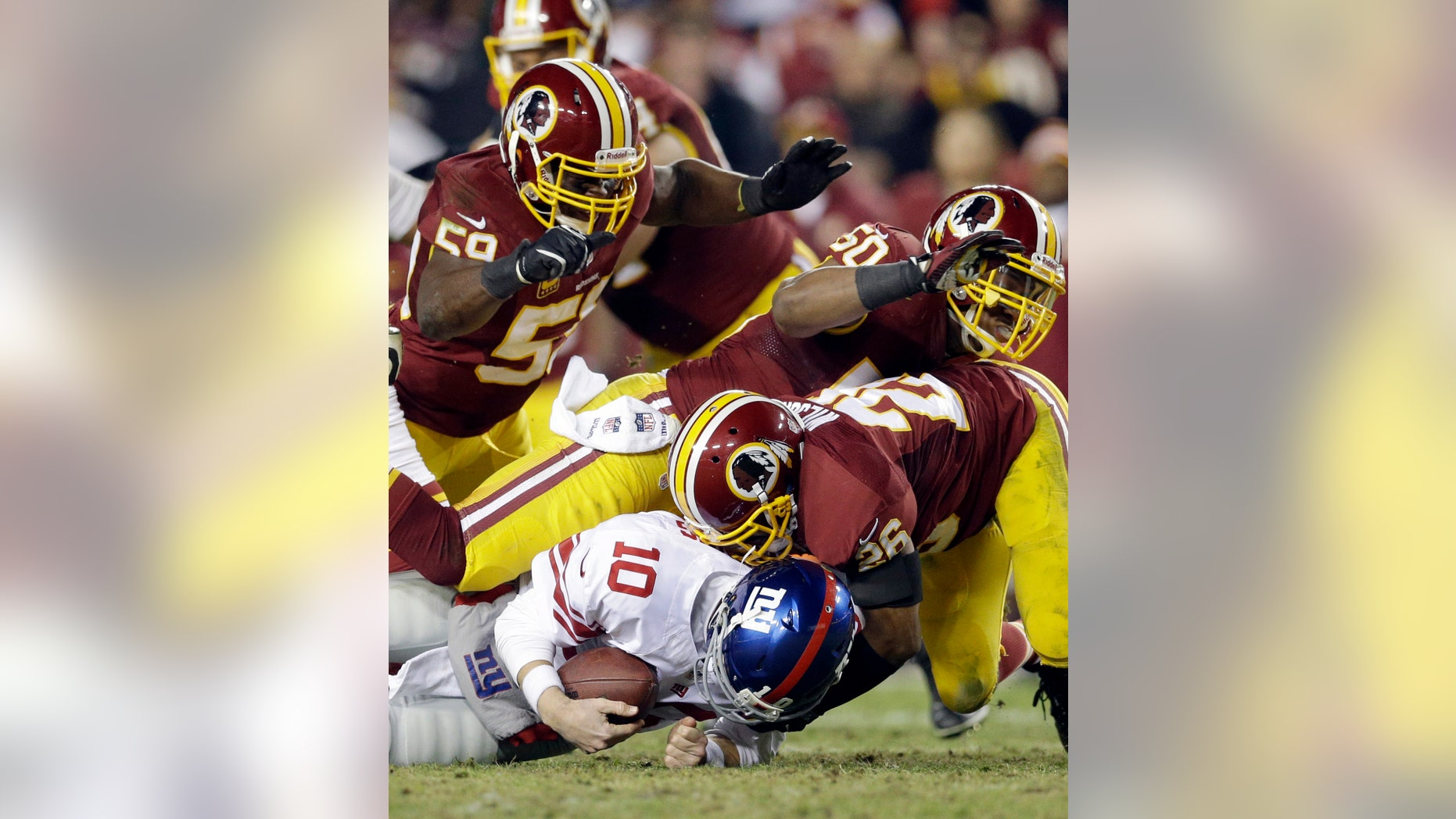 New York Giants quarterback Eli Manning (10) is sacked by Washington Redskins inside linebacker London Fletcher (59), outside linebacker Rob Jackson (50)  and cornerback Josh Wilson during the second half of an NFL football game Sunday, Dec. 1, 2013, in Landover, Md. The Giants won 24-17. (AP Photo/Patrick Semansky)