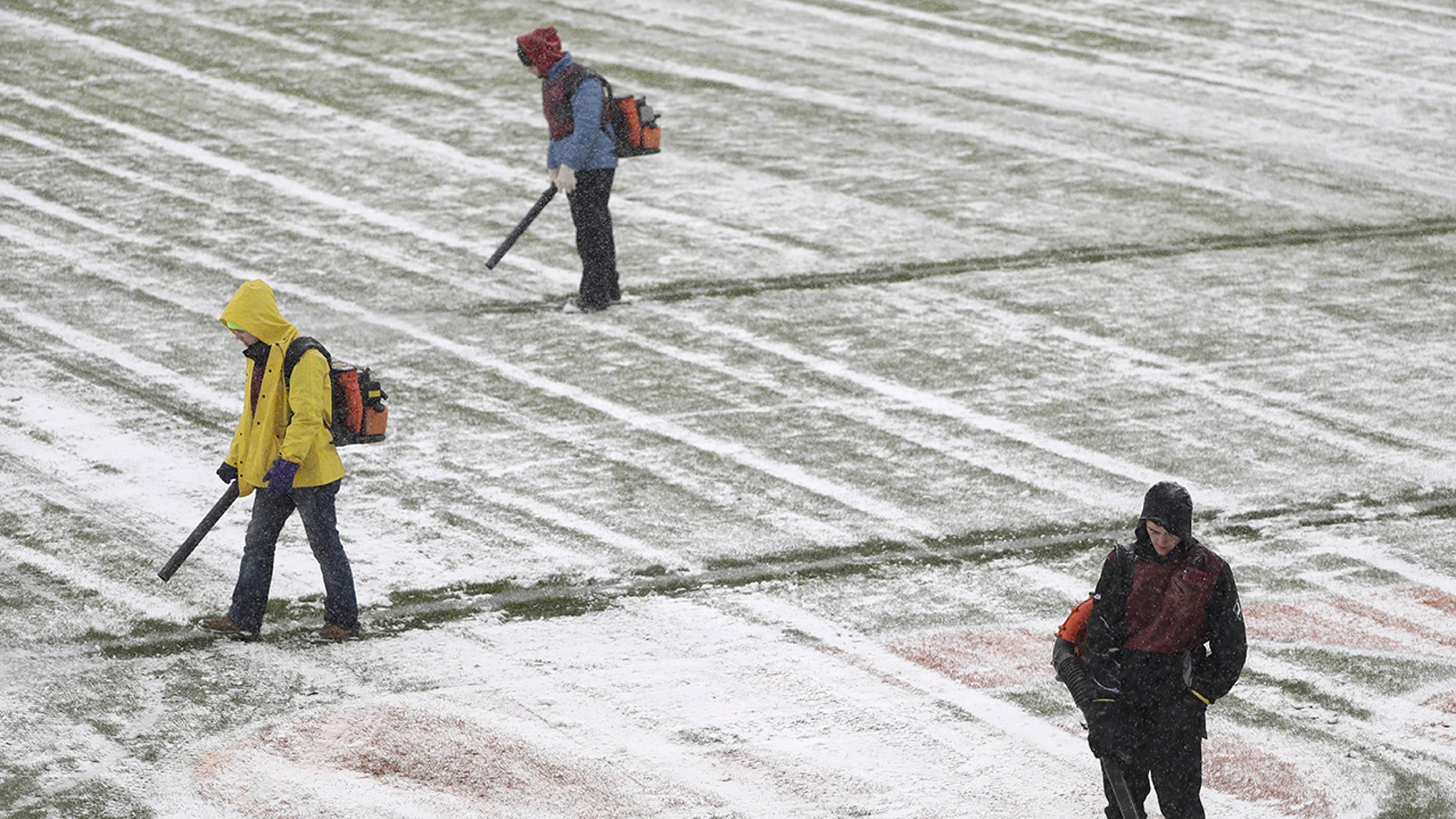 Workers clear snow from Soldier Field before an NFL football game between the Chicago Bears and Cleveland Browns in Chicago, Sunday, Dec. 24, 2017. (AP Photo/Charles Rex Arbogast)