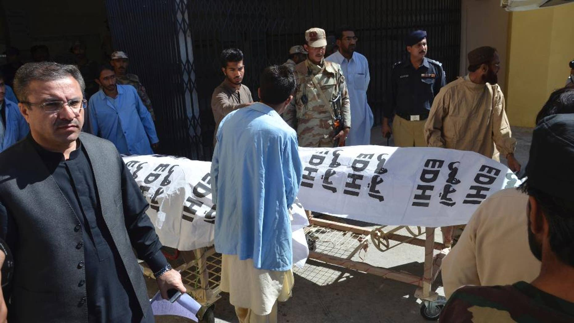 People carry dead bodies of paramilitary officers killed by gunmen in Quetta, Pakistan, Friday, Oct. 14, 20165. Gunmen riding on motorcycles shot and killed three paramilitary officers Friday in the southwestern Pakistani city of Quetta before fleeing, official said. The attack on FC guards, the Islamic State group claimed responsibility for the killing the three guards on street in Quetta, though there is no visible sign of IS in the city. (AP Photo/Arshad Butt)