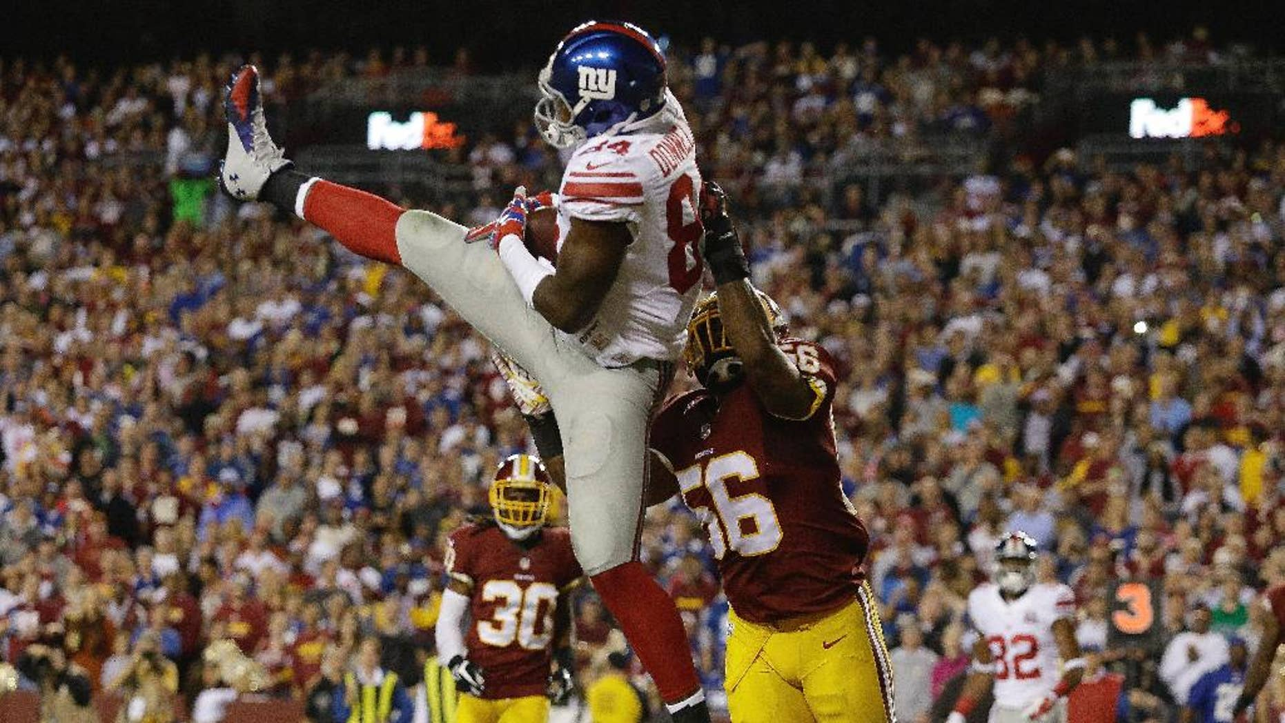 New York Giants tight end Larry Donnell (84) pulls in a touchdown pass under pressure from Washington Redskins inside linebacker Perry Riley (56) during the first half of an NFL Thursday night football game in Landover, Md., Thursday, Sept. 25, 2014. (AP Photo/Patrick Semansky)