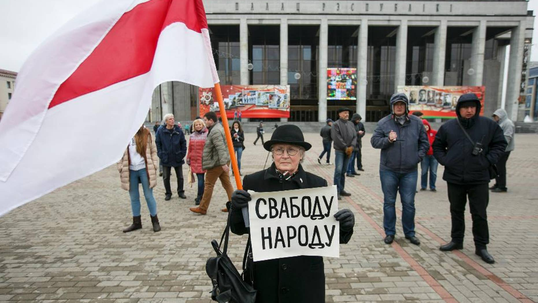 A protester holds a poster reading 'Freedom for the people' and an old Belarus flag, a symbol of protest, during an opposition rally in Minsk, Belarus, Monday, May 1, 2017. The protesters marched through central Minsk calling for the government to step down and for free elections to be held. (AP Photo)