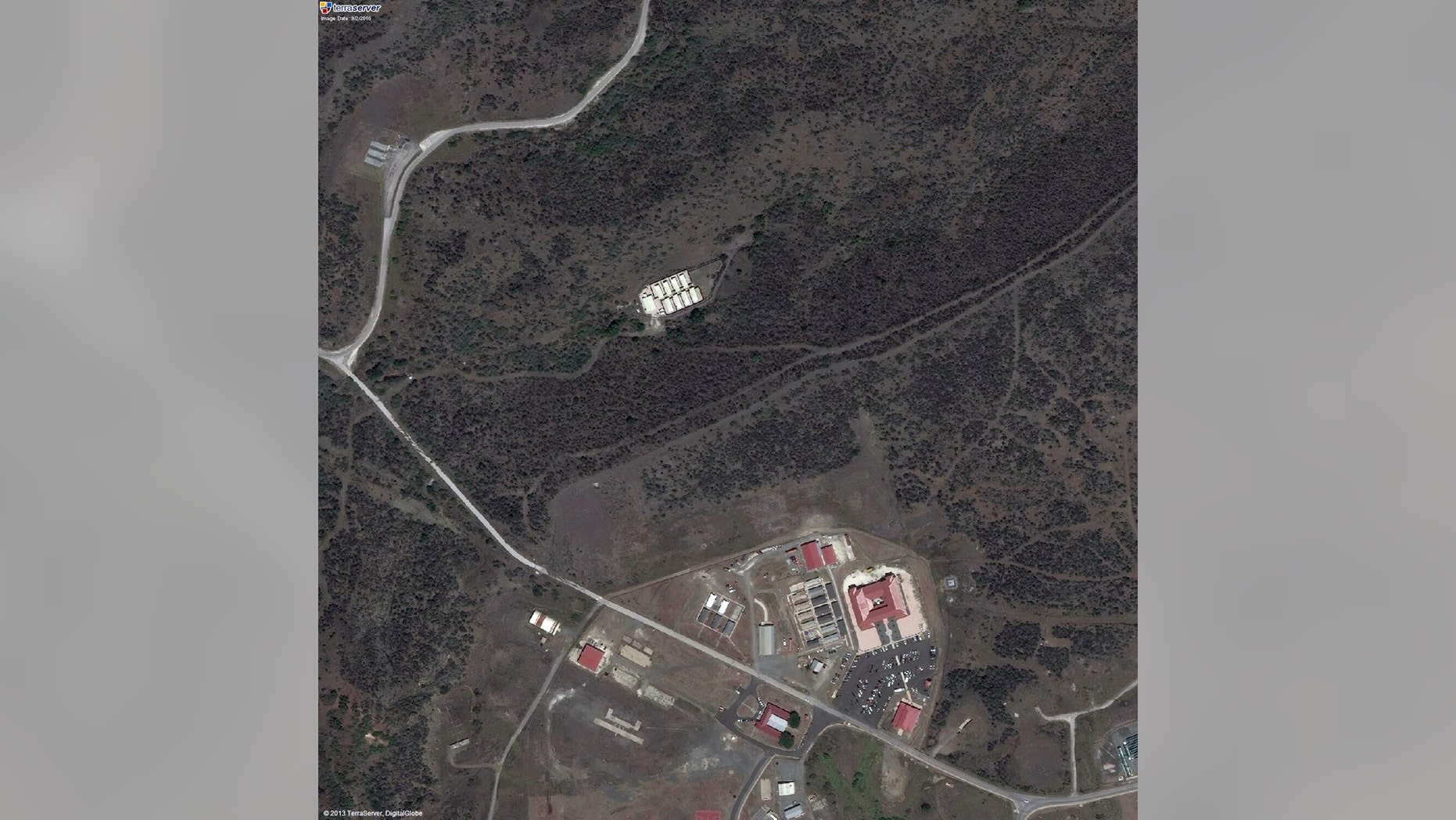 This satellite image provided by TerraServer.com and DigitalGlobe shows an image captured on Sept. 2, 2010, shows a portion of Naval Station Guantanamo Bay, Cuba, including the secret facility known as Penny Lane, upper middle in white. In the early years after 9/11, the CIA turned a handful of prisoners at the secret facility into double agents and released them. Current and former U.S. officials tell The Associated Press that the program helped kill terrorists. The program was carried out in the secret facility, built a few hundred yards from the administrative offices of the prison in Guantanamo Bay, bottom of image. The eight small cottages were hidden behind a ridge covered in thick scrub and cactus. (AP Photo/TerraServer.com and DigitalGlobe)