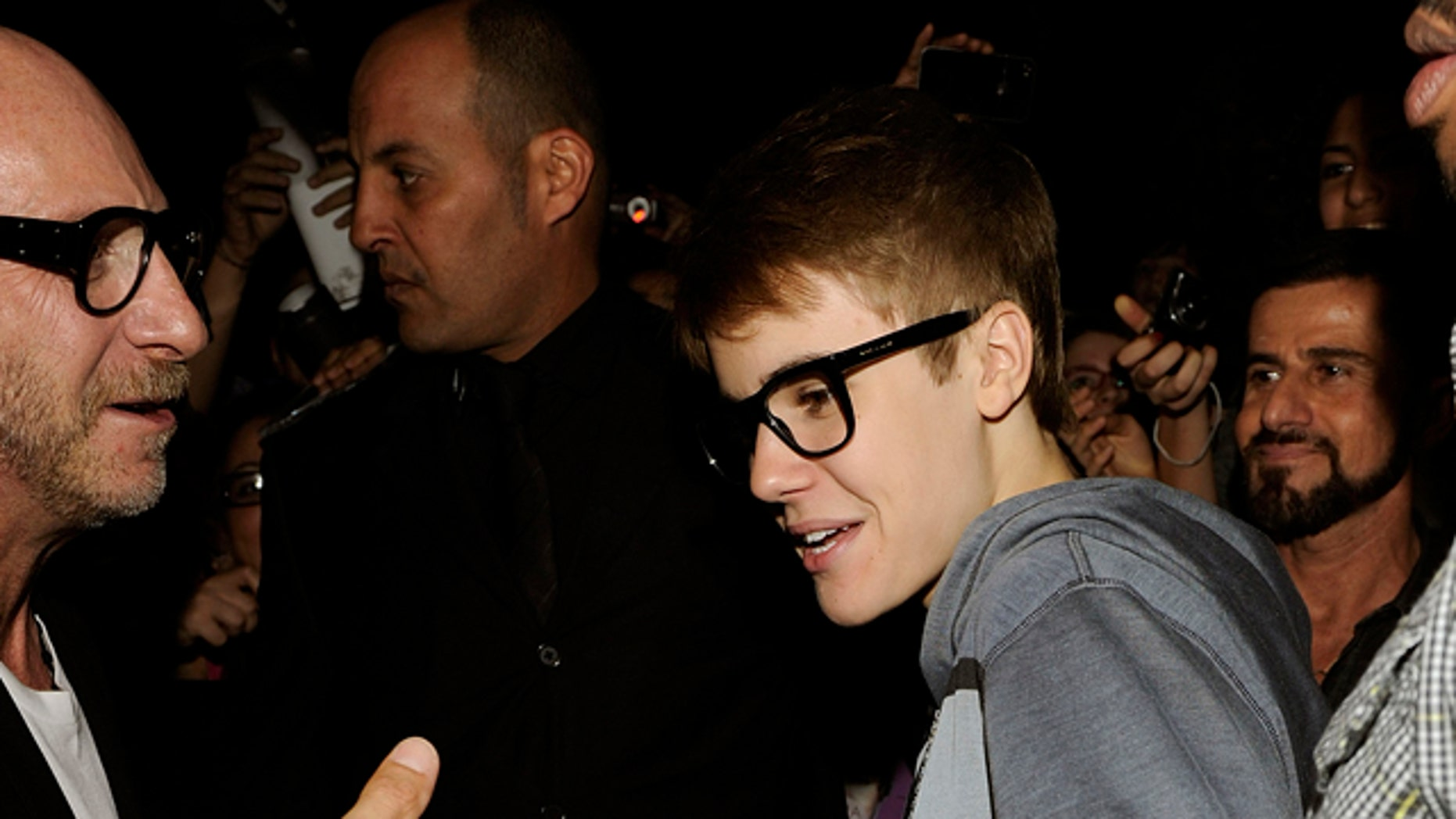 April 9, 2011: Canadian Pop singer Justin Bieber is welcomed by Domenico Dolce, left, as arrives at the Gold Restaurant after his concert in Milan , Italy
