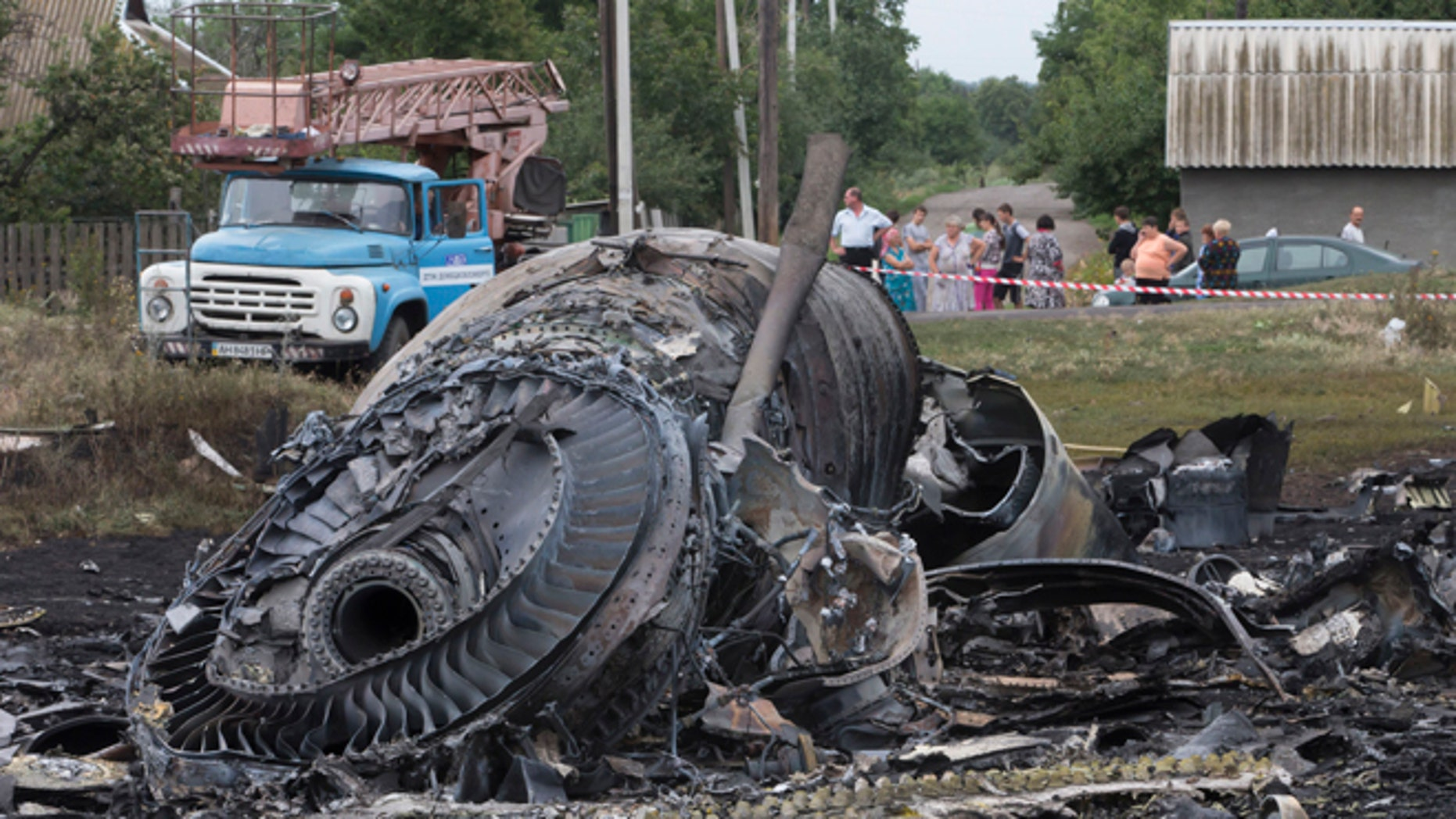 Local citizens, background, look at the site of a crashed Malaysia Airlines passenger plane near the village of Rozsypne, Ukraine, eastern Ukraine Friday, July 18, 2014. Rescue workers, policemen and even off-duty coal miners were combing a sprawling area in eastern Ukraine near the Russian border where the Malaysian plane ended up in burning pieces Thursday, killing all 298 aboard. (AP Photo/Dmitry Lovetsky)