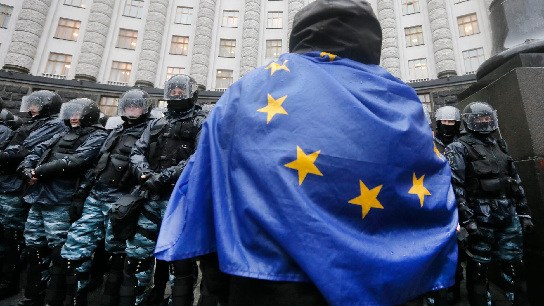 An  opposition supporter draped in an EU flag,  attends a protest in front of the Ukrainian Cabinet of Ministers in Kiev, Ukraine, Monday, Nov. 25, 2013. Hundreds of angry Ukrainians on Monday clashed with riot police outside the government building as protests continued in Kiev over the government's abrupt decision to pause integration with the West and tilt toward Moscow. The scuffle Monday morning follows a large protest in the heart of Kiev Sunday, the biggest since the 2004 Orange Revolution that brought a pro-Western government to power. Tens of thousands of people turned up to protest President Viktor Yanukovych's decision to snub a potentially historic deal with the EU and focus on ties with Moscow, after immense pressure from Russia. (AP Photo/Efrem Lukatsky)