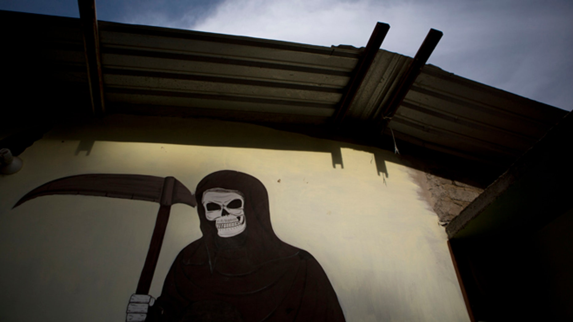 A mural of La Santa Muerte, or Saint Death, decorates the wall of a community center in Colonias, Michoacan state, Mexico, where vigilantes met with the families of a Tuesday shooting that took place in nearby Apatzingan, on Thursday, Jan. 8, 2015.  Confrontations in Apatzingan began Tuesday when federal forces moved in to take control of city hall, which had been held for days by civilians whose demands and identities were unclear, according to Michoacan state Commissioner Alfredo Castillo. The second clash came when gunmen attacked soldiers who were transporting the seized vehicles to an impound lot, Castillo said. However, family members and witnesses tell a different story, one with a higher death toll. (AP Photo/Rebecca Blackwell)