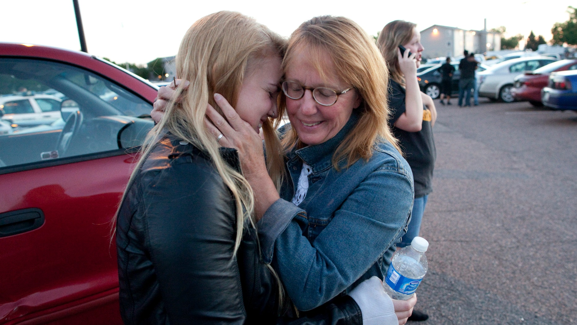 July 20, 2012: Emma Goos, 19, hugs her mother, Judy Goos, outside Gateway High School where witnesses were brought for questioning Friday, in Aurora, Colo. Emma was in the third row of the theater of the new Batman movie when the shooter entered. She helped apply pressure to a man's head who was injured.
