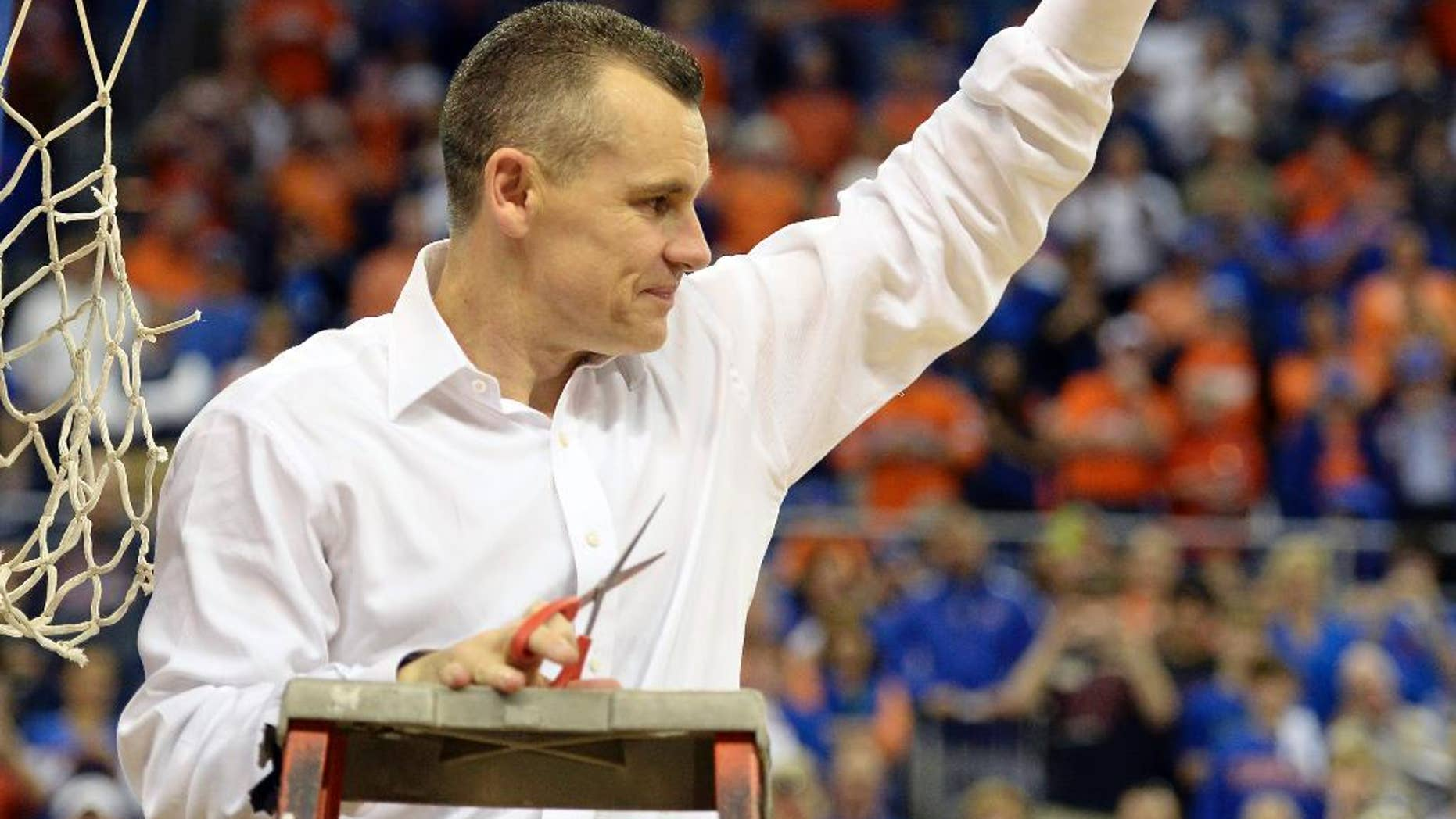 Florida coach Billy Donovan holds up a piece of the net after the Gators became the first team in Southeastern Conference history to go 18-0 in league pla, Saturday, March 8, 2014 in Gainesville, Fla. Florida defeated Kentucky 84-65 Saturday in an NCAA college basketball game. (AP Photo/Phil Sandlin)