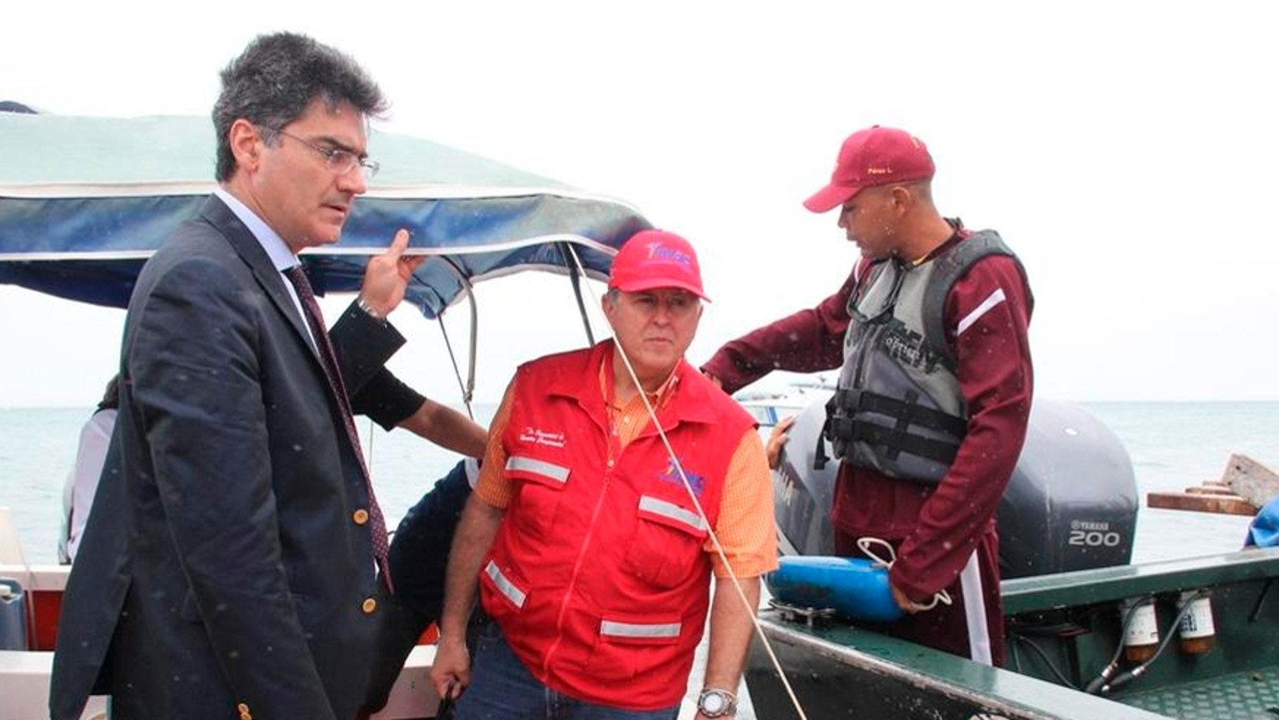 In this photo provided by Venezuela's Ministry of the Interior and Justice Press Office, Italy's ambassador to Venezuela Paolo Serpi, left, speaks with rescue team members prior to their continued search for a missing plane off Los Roques, Venezuela, Monday, Jan. 7, 2013.  The search for a missing plane carrying Italian fashion executive Vittorio Missoni and five other people has entered its fourth straight day on Monday with no signs of the aircraft. The small, twin-engine plane was reported missing hours after taking off Friday from Los Roques, a string of islands and islets popular among tourists for their white beaches and coral reefs.  (AP Photo/Venezuela Ministry Interior and Justice Office Press)