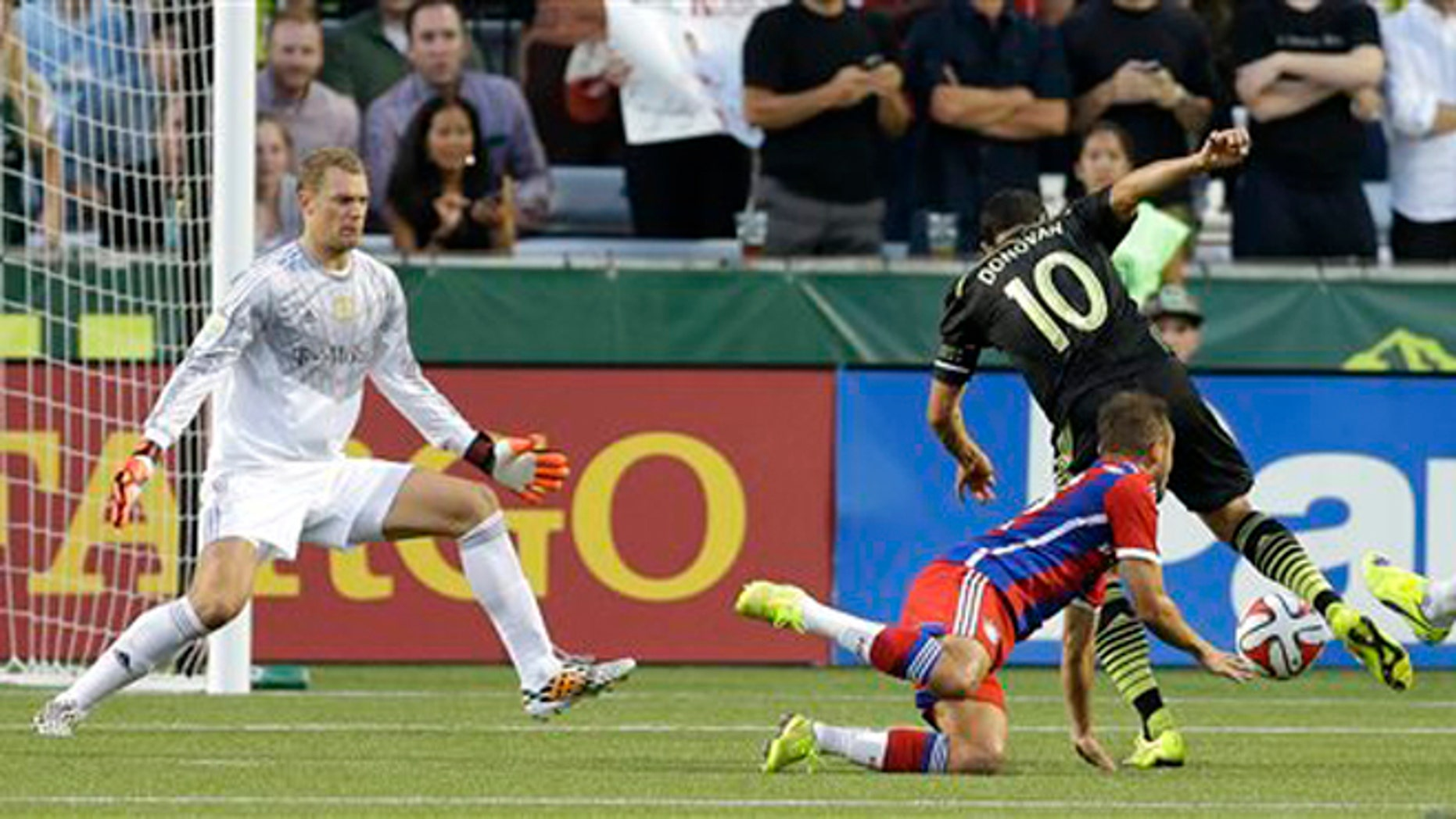 Los Angeles Galaxy forward Landon Donovan (10) scores the go-ahead goal on Bayern Munich goalkeeper Manuel Neuer, left, and around the defense of Rafinha, second from left, in the second half of the MLS All-Star soccer game, Wednesday, Aug. 6, 2014, in Portland, Ore. The MLS All-Stars won 2-1. (AP Photo/Ted S. Warren)