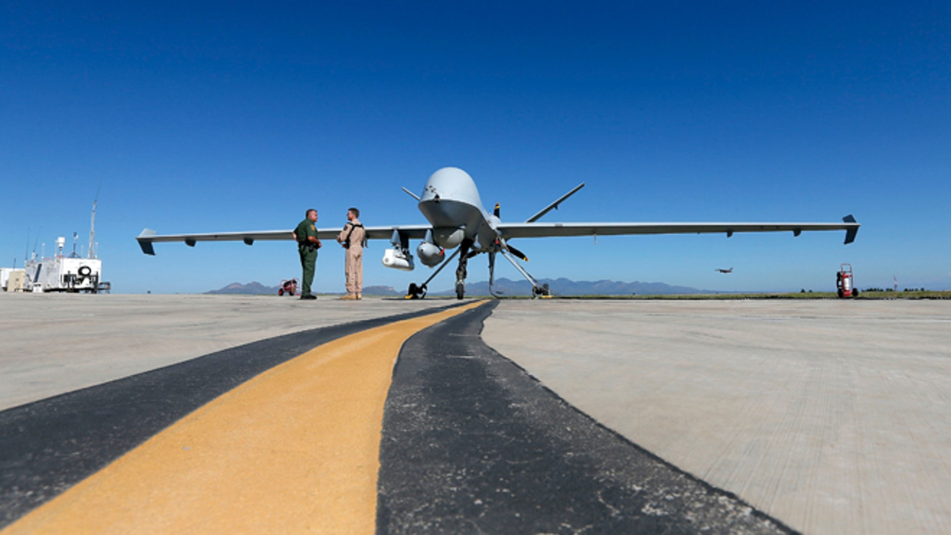 Lothar Eckardt, right, executive director of National Air Security Operations at U.S. Customs and Border Protection, speaks with a Customs and Border Patrol agent prior to a drone aircraft flight, Wednesday, Sept 24, 2014 at Ft. Huachuca in Sierra Vista, Ariz. The U.S. government now patrols nearly half the Mexican border by drones alone in a largely unheralded shift to control desolate stretches where there are no agents, camera towers, ground sensors or fences, and it plans to expand the strategy to the Canadian border. It represents a significant departure from a decades-old approach that emphasizes boots on the ground and fences. (AP Photo/Matt York)
