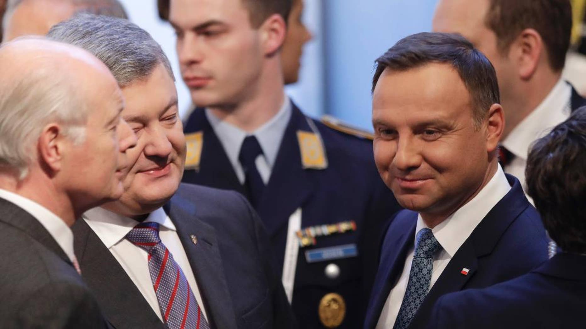 Polish President Andrzej Duda,right, and the president of Ukraine Petro Poroshenko chat during the Munich Security Conference in Munich, southern Germany, Friday, Feb. 17, 2017. The annual weekend gathering is known for providing an open and informal platform to meet in close quarters. (AP Photo/Matthias Schrader)