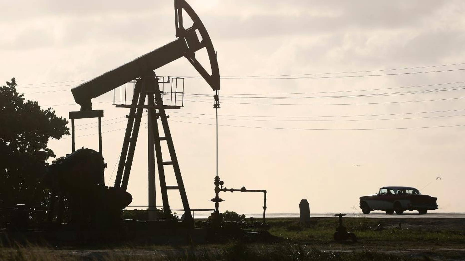 FILE - In this July 11, 2014 file photo, an oil well pump operates in Boca de Jaruco, Cuba. Officials are warning of tough times with authorities ordering energy-saving measures and some state entities reducing hours of operation.  (AP Photo/Desmond Boylan, File)