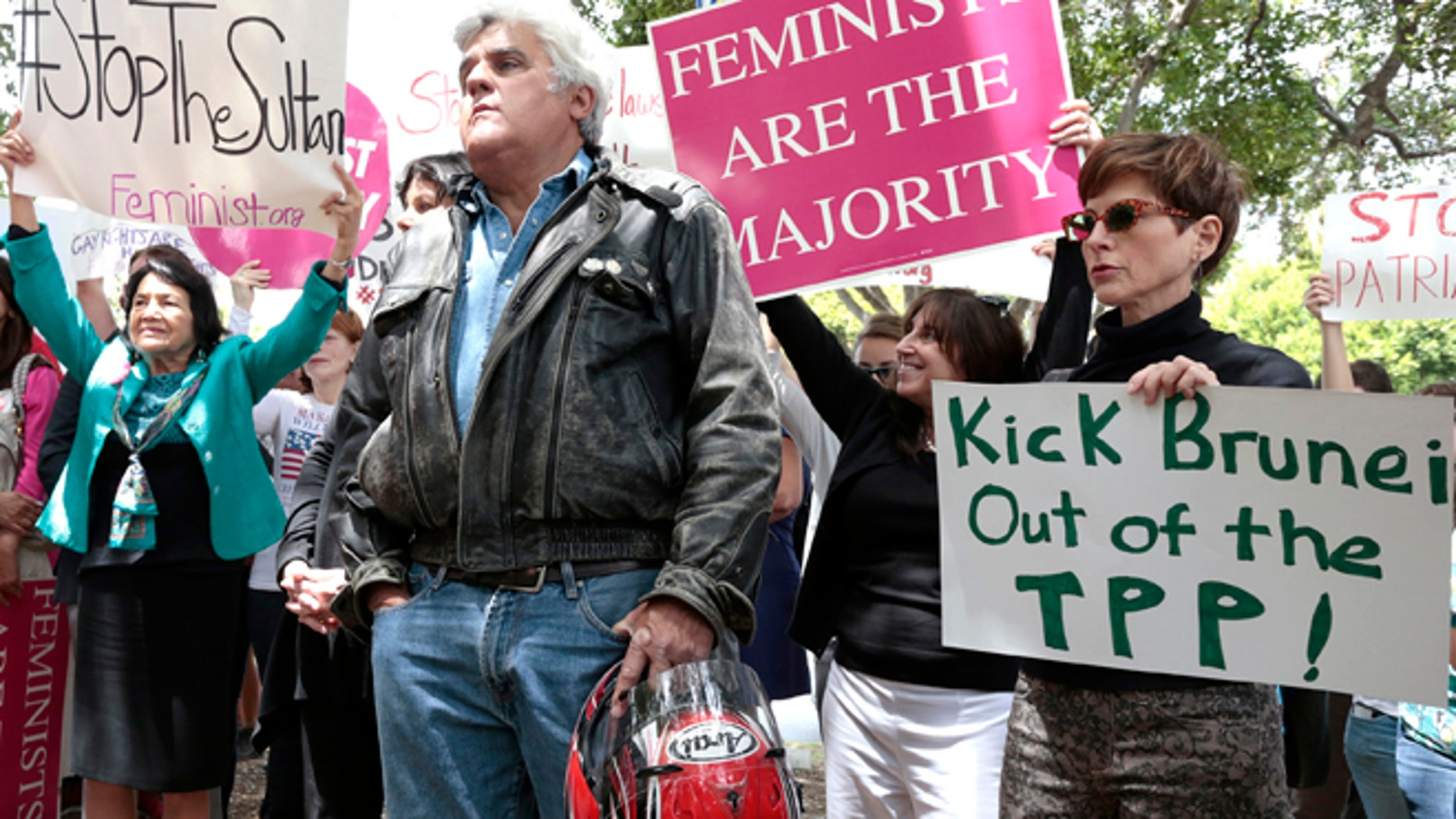 TV personality Jay Leno (C) attends a rally protesting against Brunei's new strict sharia law penal code outside the Beverly Hills Hotel, which is owned by the Sultan of Brunei, in Beverly Hills, California May 5, 2014. The sultanate of Brunei becomes the first East Asian country to introduce Islamic criminal law, the latest example of a deepening religious conservatism that has also taken root in parts of neighbouring Malaysia and Indonesia. REUTERS/Jonathan Alcorn   (UNITED STATES - Tags: CIVIL UNREST RELIGION ENTERTAINMENT) - RTR3NWAD