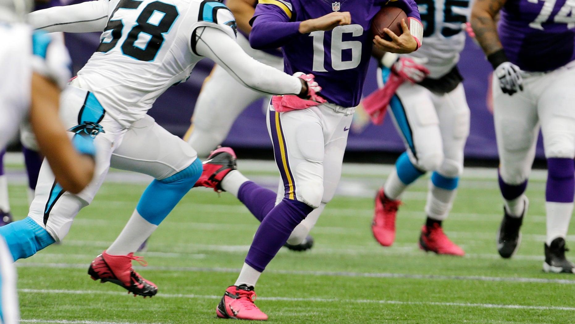 Carolina Panthers outside linebacker Thomas Davis, left, chases down Minnesota Vikings quarterback Matt Cassel (16) as he runs during the first half of an NFL football game in Minneapolis, Sunday, Oct. 13, 2013. (AP Photo/Ann Heisenfelt)