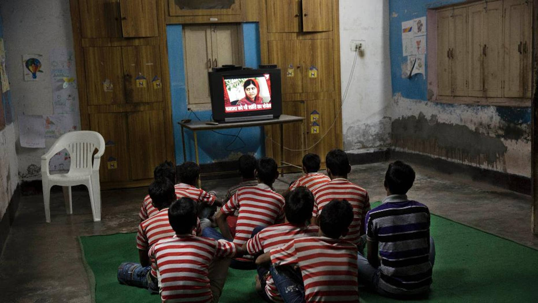 Children rescued by the workers of the NGO Bachpan Bachao Andolan or Save Childhood Movement, run by Kailash Satyarthi, watch the news of Pakistan's Malala Yousafzai on television at the Mukti Ashram in New Delhi, India, Friday, Oct. 10, 2014. Satyarthi and Malala jointly won the Nobel Peace Prize on Friday for working to protect children from slavery, extremism and child labor at great risk to their own lives. (AP Photo/Bernat Armangue)