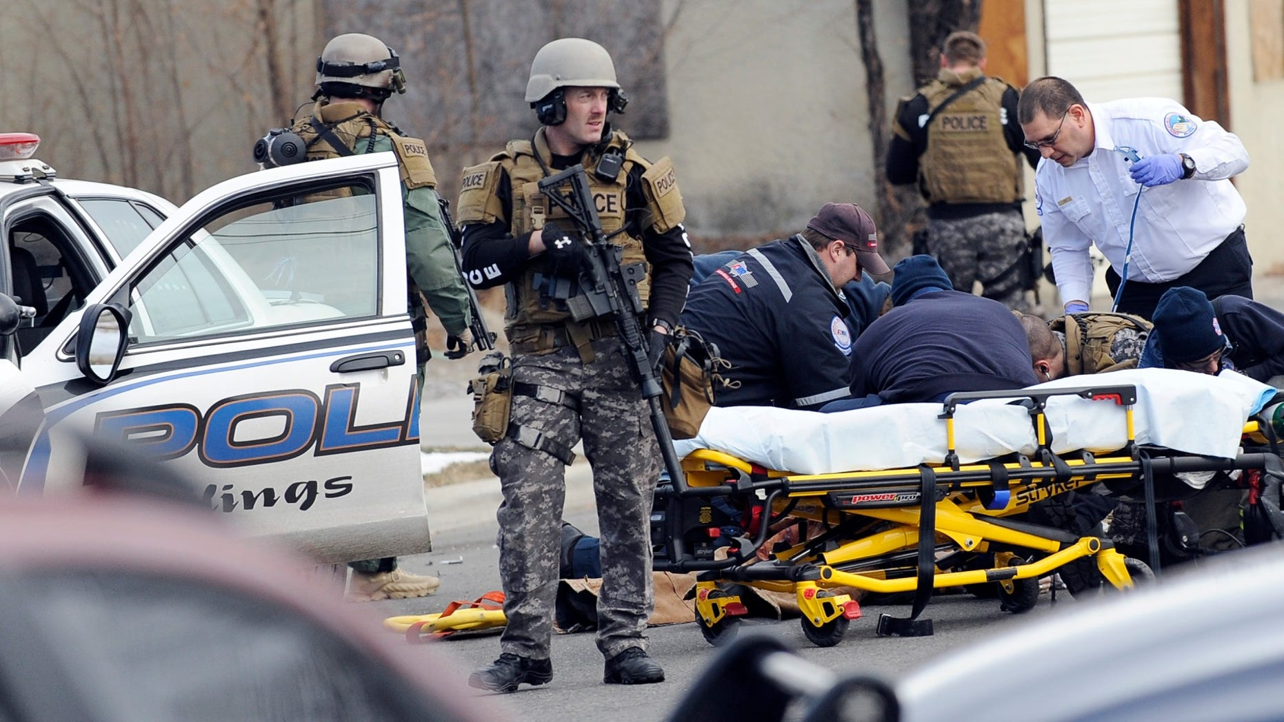 In this Sunday, Jan. 6, 2013 photo, SWAT team members stand guard as a man is given CPR after a standoff with police and the SWAT team in Billings, Mont. The standoff ended with the death of a handcuffed burglary suspect who hit a Montana police officer with his own patrol car before the officer opened fire. (AP Photo/The Billings Gazette, James Woodcock)