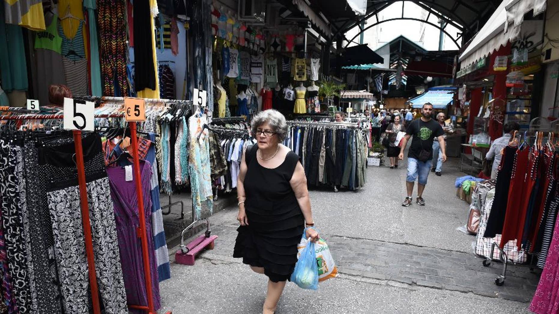 An elderly woman holds shopping bags as she leaves from a market area in the northern Greek port city of Thessaloniki, Wednesday, June 10, 2015. Greece has three weeks left to conclude a deal with its creditors before its bailout program expires at the end of the month. It is desperate for the disbursal of the final 7.2 billion euros in rescue loans, without which it cannot continue to repay its international debts. (AP Photo/Giannis Papanikos)