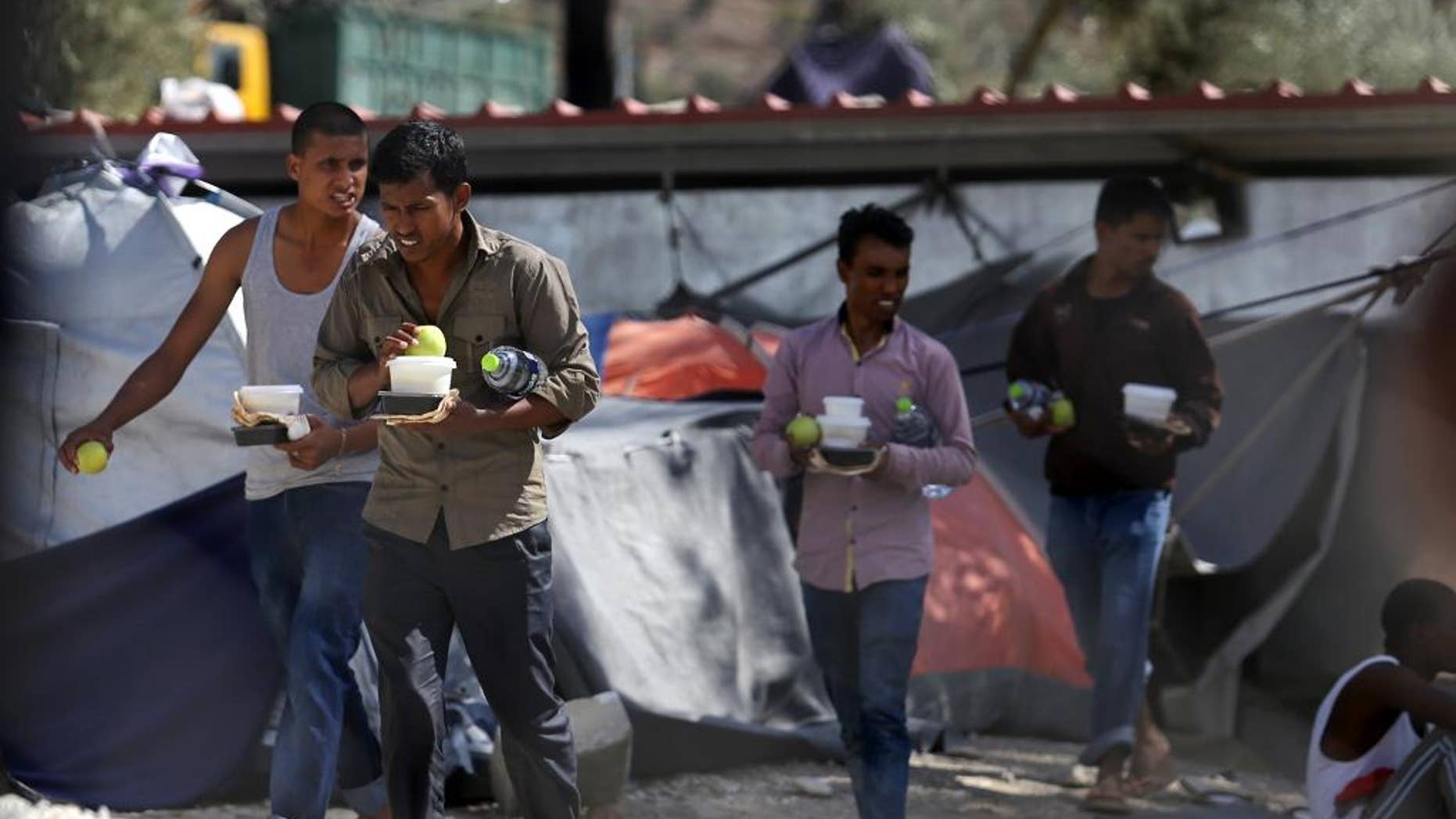 Migrants carry food at the Moria refugee camp on the northeastern Greek island of Lesbos, on Tuesday, Sept. 20, 2016, after a fire gutted the camp following protests at the camp.  Authorities of the island of Lesbos are calling for the immediate evacuation of thousands of refugees to the Greek mainland, following the fire and nine migrants suspected of starting the blaze have been arrested, authorities said Tuesday. (Dimitris Tosidis/InTime News via AP)