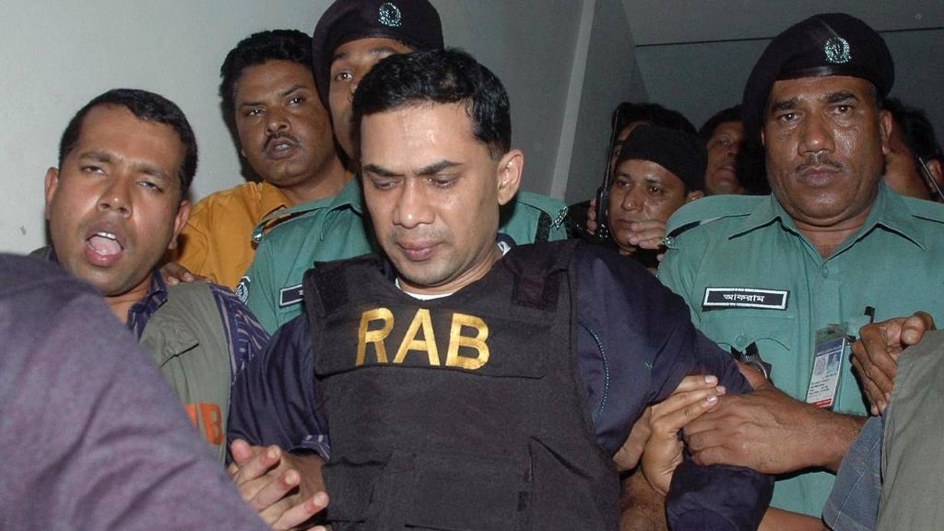 FILE - In this March 8, 2007 file photo, Tarique Rahman, center, who was charged with receiving bribes, is escorted by Bangladeshi security personnel to a court in Dhaka, Bangladesh. Bangladesh's High Court on Thursday, July 21, 2016 sentenced Rahman the son of the country's top opposition leader Khaleda Zia to seven years in jail in a money laundering case, overturning an acquittal handed down by a lower court. (AP Photo/Indrajit Kumer Ghosh, File)