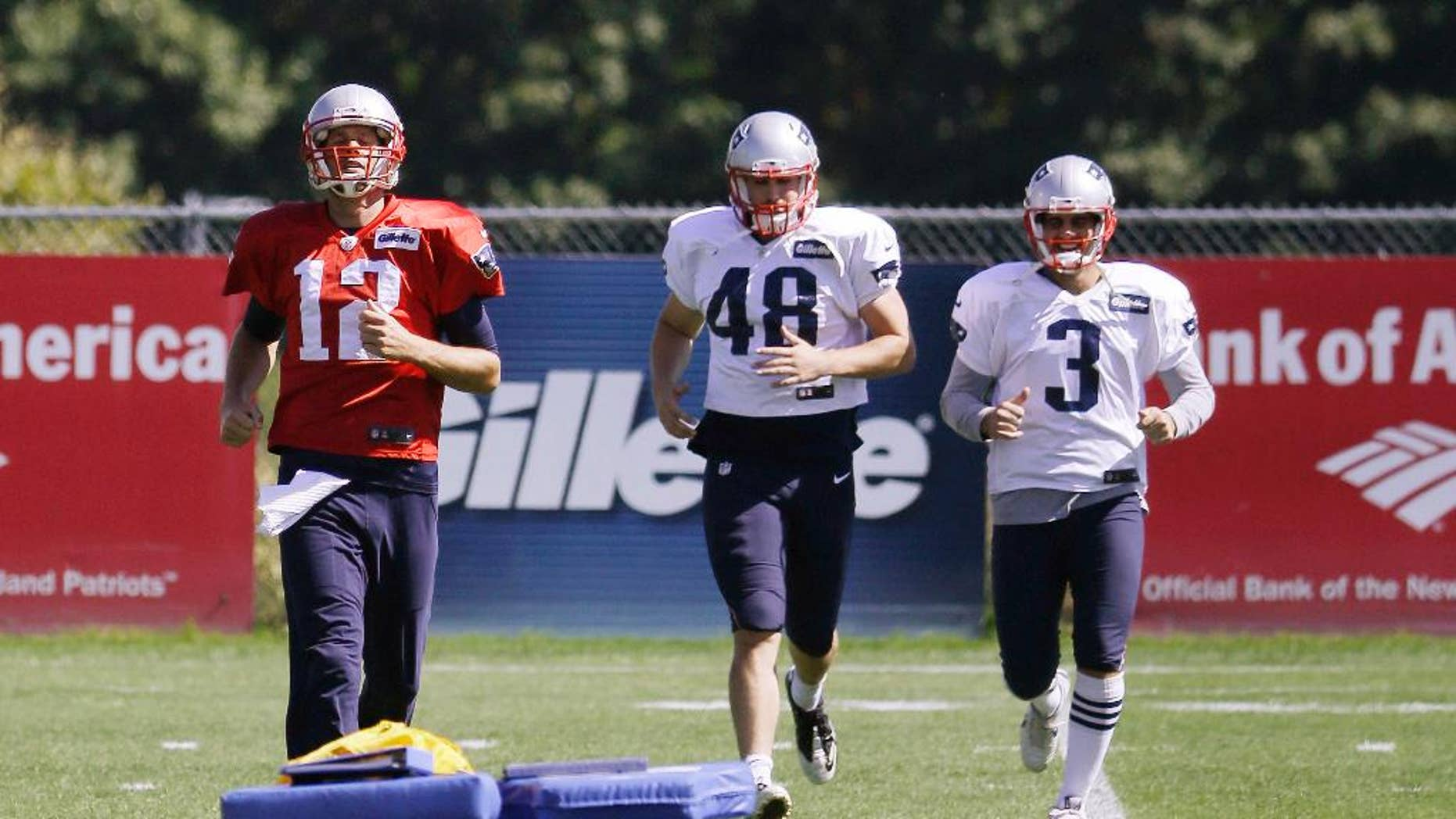 New England Patriots quarterback Tom Brady (12), long snapper Danny Aiken (48) and kicker Stephen Gostkowski (3) run during a stretching session before practice begins at the NFL football team's facility Wednesday, Sept. 17, 2014 in Foxborough, Mass. (AP Photo/Stephan Savoia)
