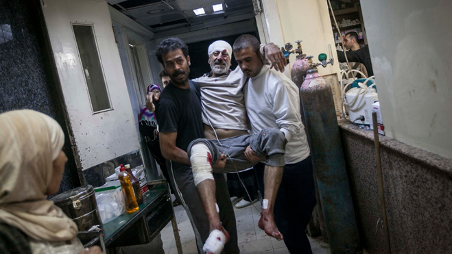 Nov. 13, 2012: A Syrian man is carried in the arms of his relatives at a hospital after he was injured by a mortar shell explosion in the Bab Al-Nayrab neighborhood of Aleppo, Syria.