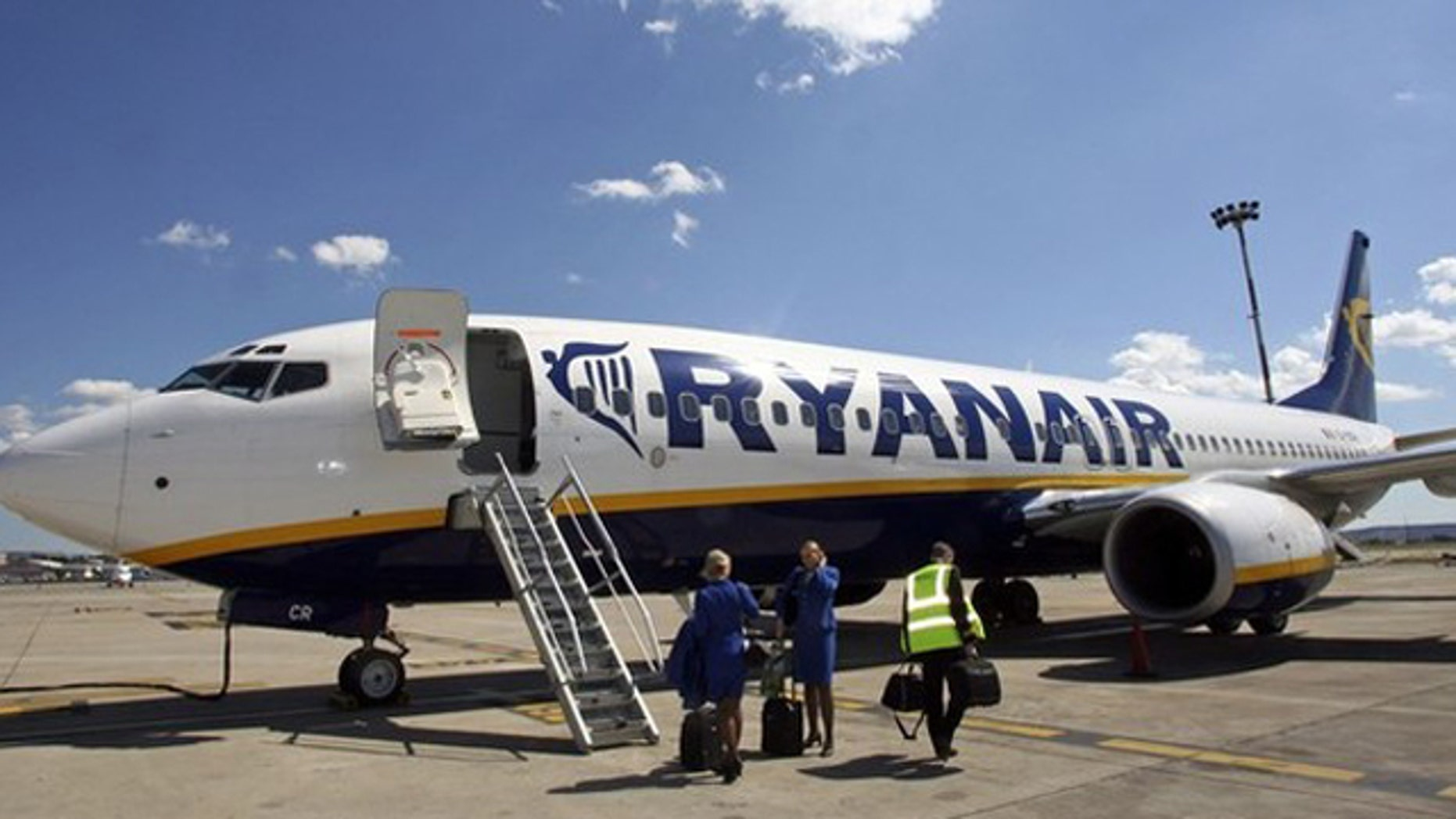 Ryanair crew stand in front of the airline's passenger jet on the tarmac of Marignane airport in Marseille in this May 10, 2006 file photo. Low-cost airline Ryanair has been charged with illegal working practices after the Irish budget airline declared 120 employees in France as working in Ireland, a justice source said on September 28, 2010.   REUTERS/Jean-Paul Pelissier/Files   (FRANCE - Tags: TRANSPORT EMPLOYMENT BUSINESS CRIME LAW)