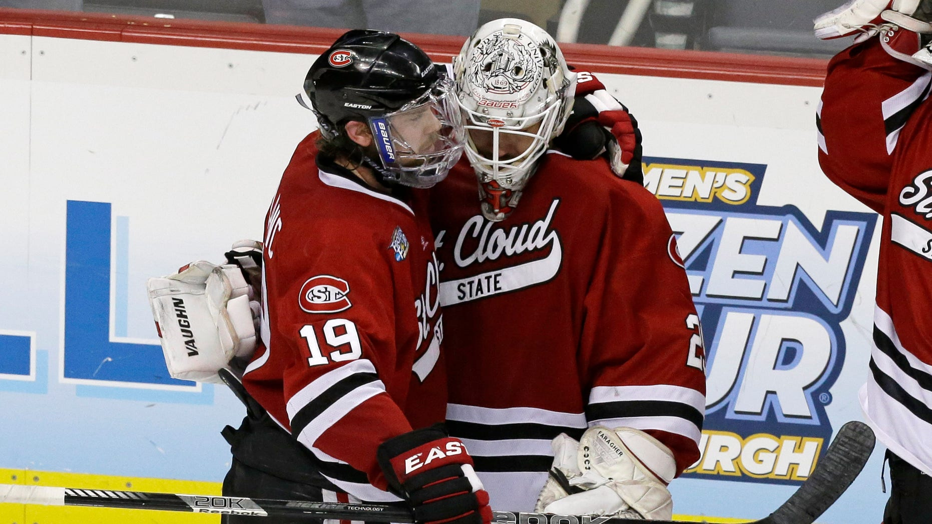 St. Cloud State goalie Ryan Faragher, right, is hugged by Drew LeBlanc (19) after losing 4-1 to Quinnipiac in an NCAA college hockey Frozen Four semifinal game in Pittsburgh, Thursday, April 11, 2013. Quinnipiac faces Yale in the national championship game on Saturday. (AP Photo/Gene J. Puskar)