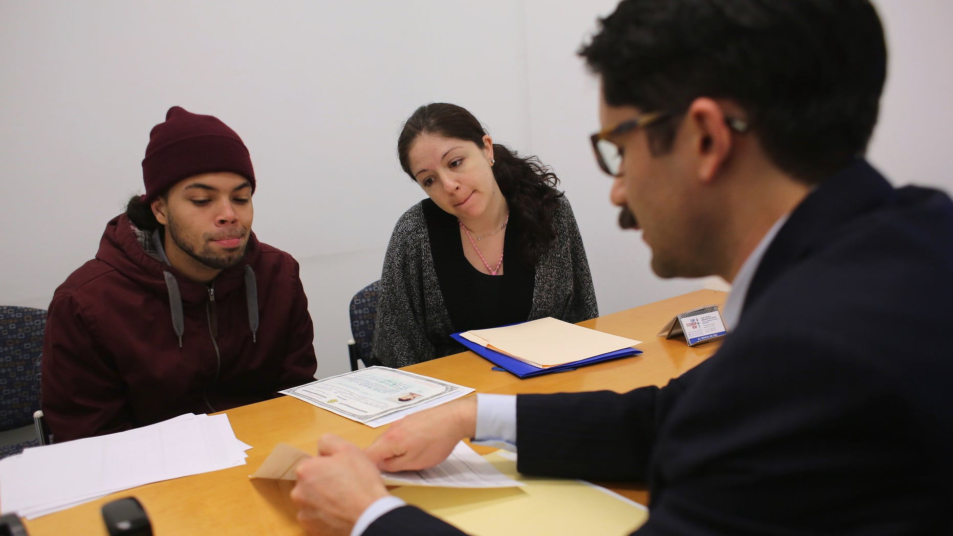 "NEW YORK, NY - JANUARY 31:  Immigration lawyer Andres Lemons advises Angel and Evie Gomez on their U.S. citizenship application on January 31, 2013 in New York City. The married couple, he from the Dominican Republic, and she from Canada are soon to have a baby and are working through the long process to become U.S. citizens. Lemons works at the CUNY Citizenship Now ""Express Center"" in New York's Washington Heights. The non-profit helps some 8,000 immigrants in the New York area navigate through the complicated process of acquiring U.S. Citizenship and provides free legal information for the immigrant community. (Photo by John Moore/Getty Images)"
