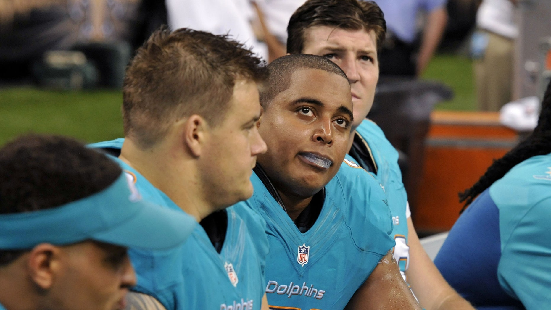FILE - In this Sept. 30, 2013 file photo, Miami Dolphins guard Richie Incognito (68), center left, and  and tackle Jonathan Martin (71), center right, sit on the bench in the second half of an NFL football game against the New Orleans Saints in New Orleans. About halfway between the start of exhibition games and the Super Bowl, there have been plenty of unwanted story lines. Bullying in the locker room, coaches collapsing, serious injuries to marquee players, the D.C. Council's call on Washington's pro football team to change its name _ examples from the past week alone. (AP Photo/Bill Feig, File)