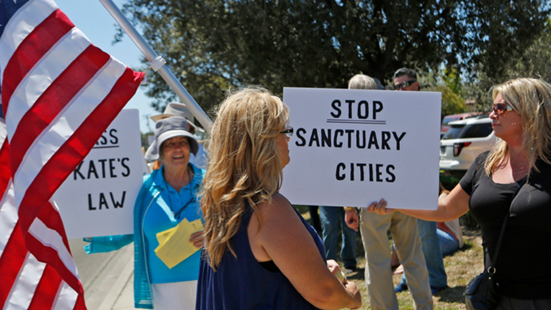 SANTA MARIA, CA - AUGUST 13: Protesters rally including Carmen Spoerer (CQ), right, who is opposed to sanctuary cities holds a sign as protesters from both sides voice their differences near the Santa Maria Courthouse after a man in the U.S. illegally Victor Martinez Ramirez and another man Jose Fernandez Villagomez pleaded not guilty today in a Santa Maria Courtroom on charges of murdering Marilyn Pharis, 64, when they broke into her home and bludgeoned her with a hammer after sexually assaulting her shot in Santa Maria on August 13, 2015. (Photo by Anne Cusack/Los Angeles Times via Getty Images)