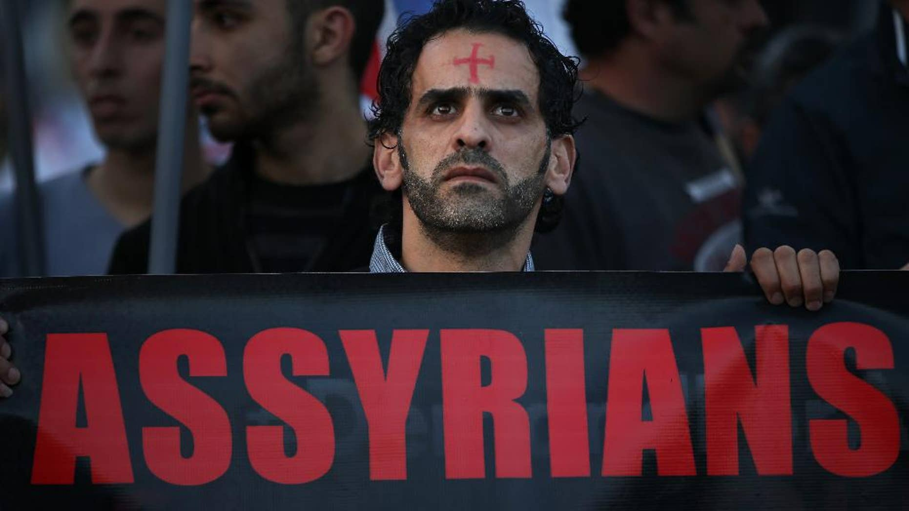 FILE - In this Saturday, Feb. 28, 2015 file photo, an Assyrian man with a red cross painted on his forehead holds a banner as he walks during a protest of several hundred people in solidarity with Christians abducted in Syria and Iraq, in downtown Beirut, Lebanon. Activists said on Saturday, March. 7, 2015, that Islamic State militants have attacked a string of predominantly Christian villages in northeastern Syria, touching off heavy clashes with Kurdish militiamen and their local allies. (AP Photo/Hussein Malla, File)