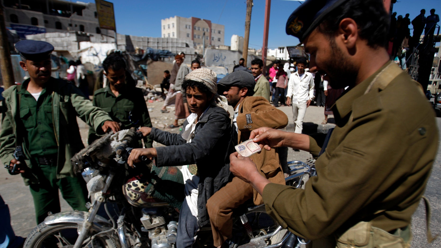 Yemeni soldiers check a motorbike driver at a checkpoint in Sanaa, Yemen, Saturday,  Jan. 5, 2013. Yemeni police have said that more than 40 security and army personnel were shot dead in drive-by attacks involving motorbikes throughout Yemen in 2012. (AP Photo/Hani Mohammed)