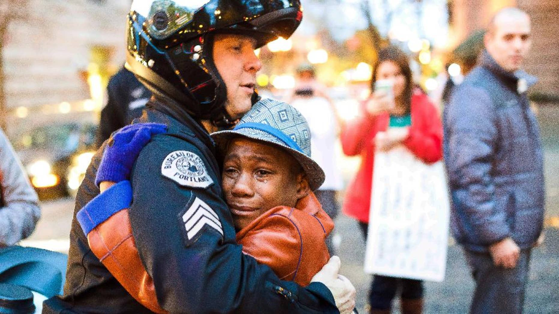 In this Tuesday, Nov. 25, 2014 photo provided by Johnny Nguyen, Portland police Sgt. Bret Barnum, left, and Devonte Hart, 12, hug at a rally in Portland, Ore., where people had gathered in support of the protests in Ferguson, Mo. (AP Photo/Johnny Huu Nguyen)