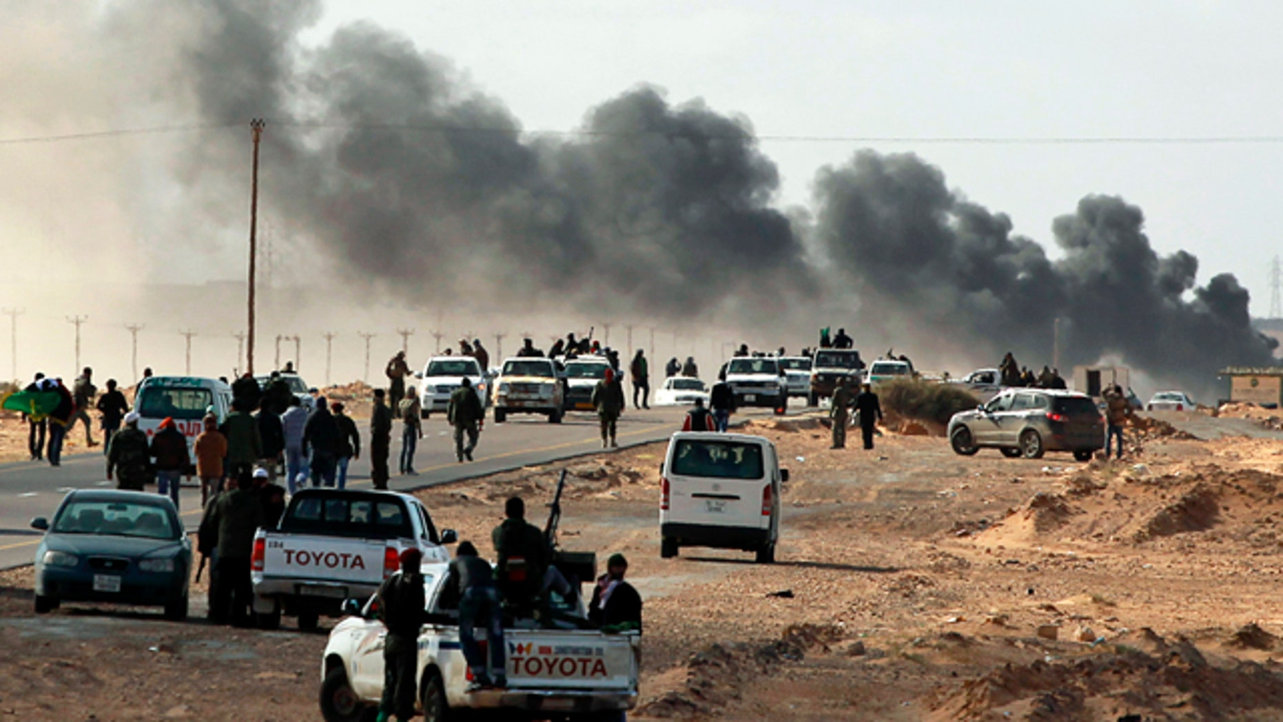 Smoke rises from heavy shelling as Libyan rebels who are part of the forces against Libyan leader Moammar Gadhafi retreat during a battle with Gadhafi's troops, outside the town of Bin Jawwad, eastern Libya, Sunday, March 6, 2011