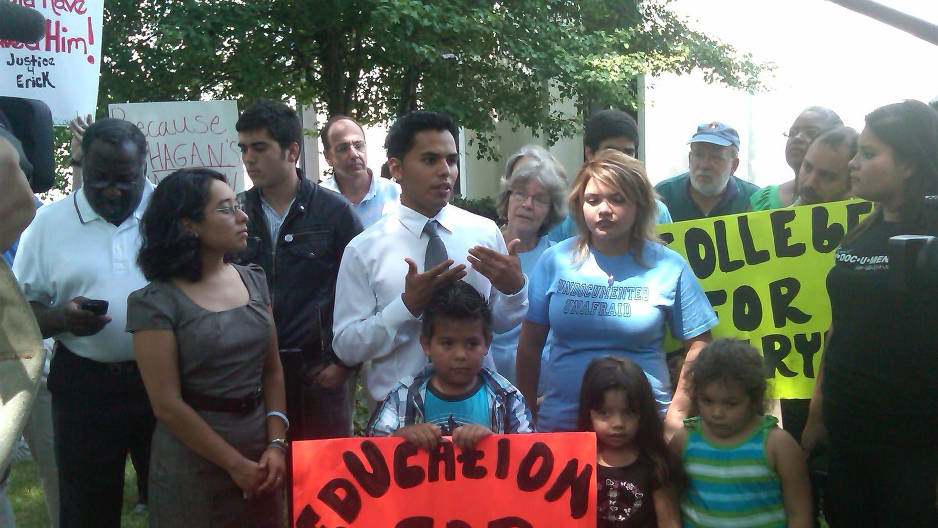 Erick Velazquillo, center wearing a tie, responds to a decision following a Charlotte, N.C., deportation hearing.