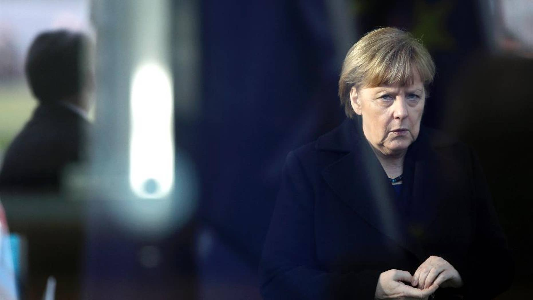 German Chancellor Angela Merkel is pictured trough a window as she waits for the arrival of NATO Secretary General Jens Stoltenberg at the chancellery in Berlin, Germany, Wednesday, Jan. 14, 2015. (AP Photo/Michael Sohn)