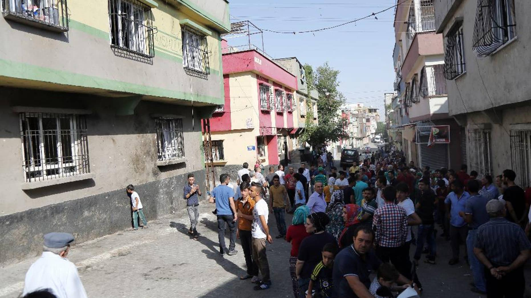 """People gather near to the scene of Saturday's bomb attack targeting an outdoor wedding party that killed dozens in Gaziantep, southeastern Turkey, Sunday, Aug. 21, 2016. Deputy Prime Minister Mehmet Simsek said the """"barbaric"""" attack in Gaziantep, near the border with Syria, on Saturday appeared to be a suicide bombing. Turkish authorities have put a temporary ban on distribution of images relating to Saturday's Gaziantep attack within Turkey. (AP Photo/Mahmut Bozarslan)"""